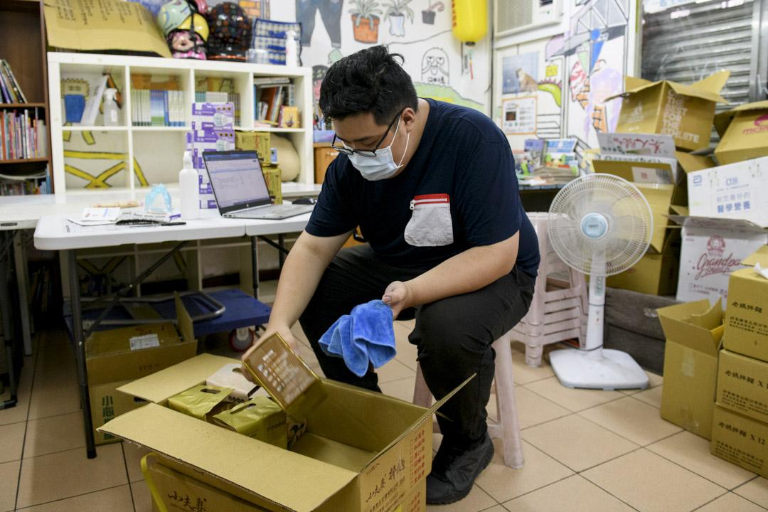 社區實踐協會社工馬明毅正在用酒精消毒收到的物資。