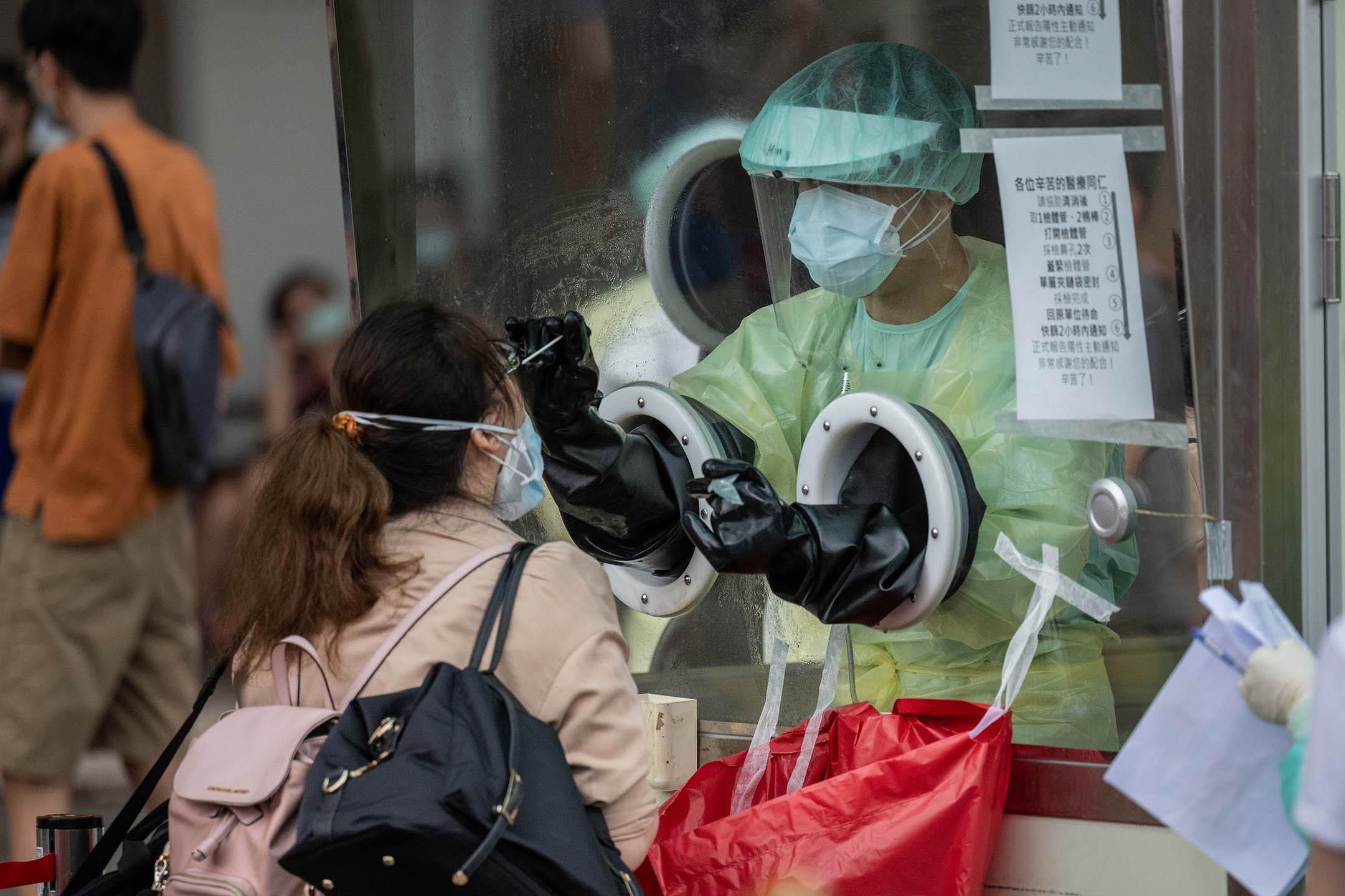 2021年5月17日台北,一名醫護人員在篩檢站從一個人身上收集樣本。