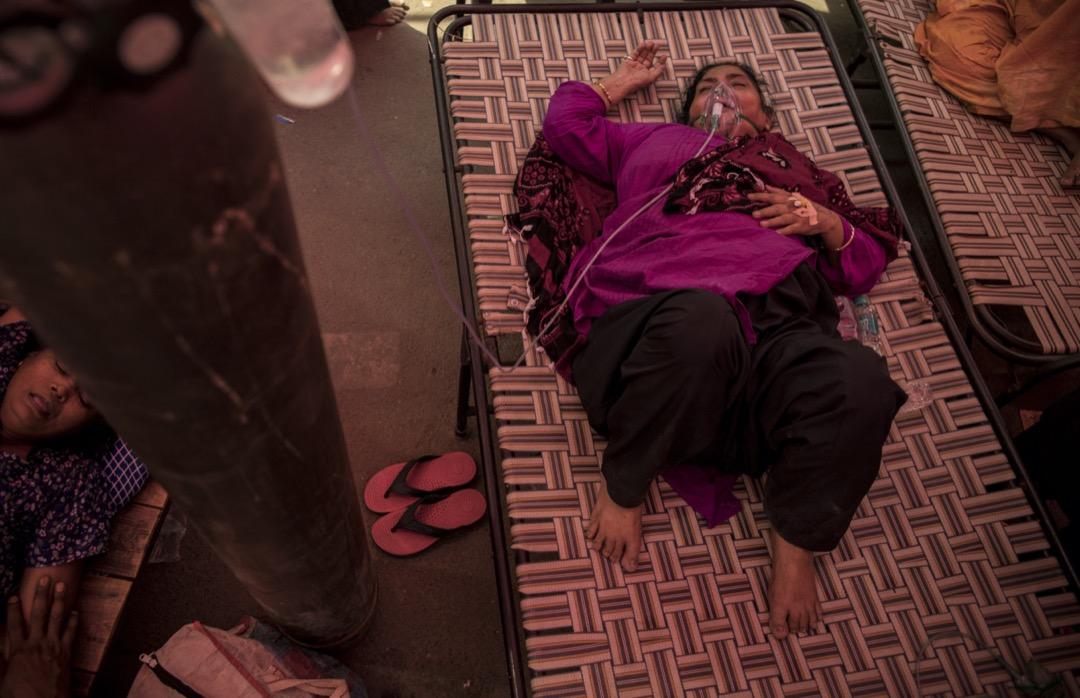 2021年5月1日,印度首都新德里,一名感染新冠病毒的女子躺在床上,透過氧氣罩呼吸。