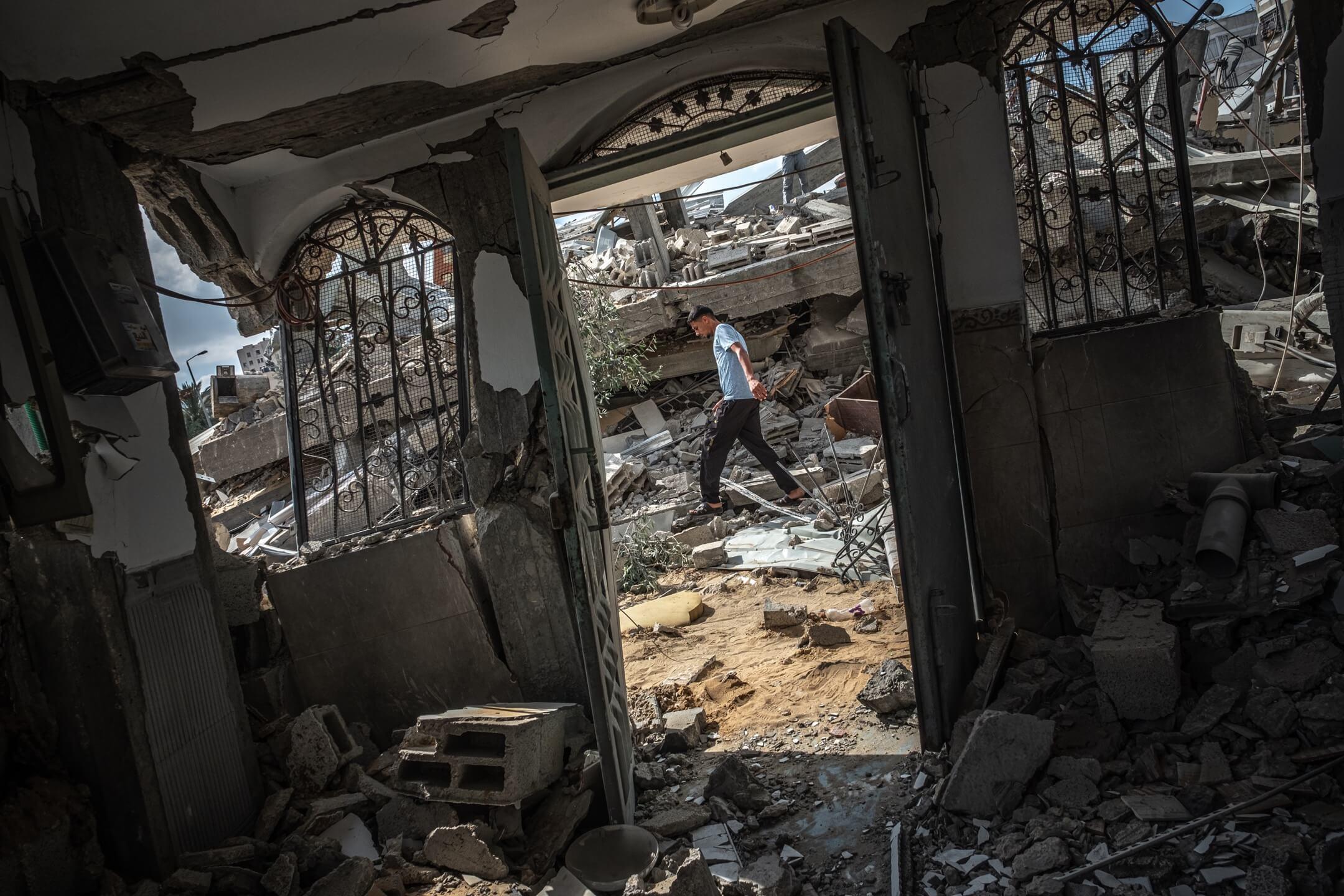 2021年5月13日,加沙市的住宅大廈被以色列空襲炸毀,一名男子在倒塌大廈的瓦礫中走過。 攝:Fatima Shbair/Getty Images