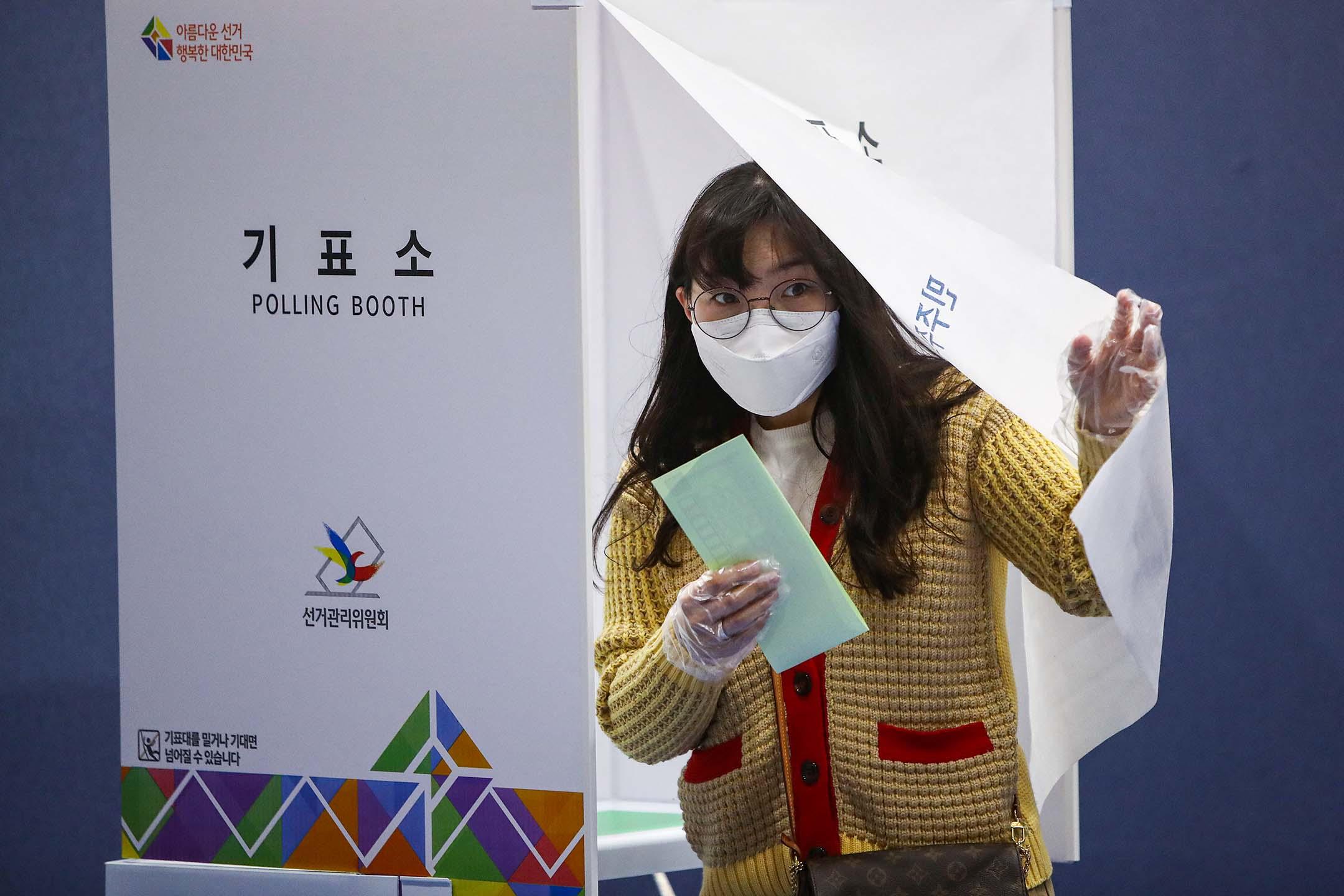 2020年4月15日韓國首爾,一名韓國婦女戴著口罩及手套在議會選舉的一個投票站內投票。