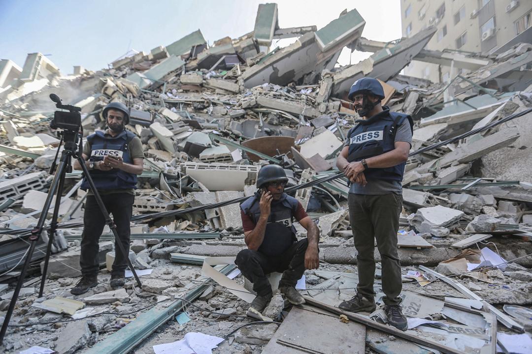 2021年5月14日在加沙地帶,半島電視台、美聯社等數家新聞機構設有辦公室的 Al-Jalaa 大樓遭受以色列轟炸,數名記者站在昔日辦公室的磚瓦之上,拍攝及報道現場情況。 攝:Mohammed Talatene / picture alliance via Getty Images