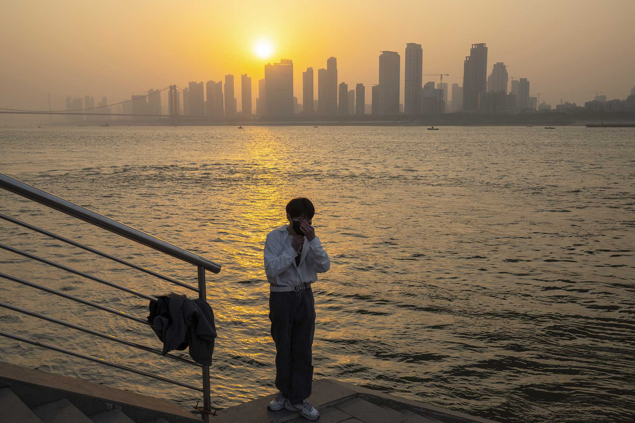 2021年1月15日武漢,一名男子戴著口罩在河岸上。