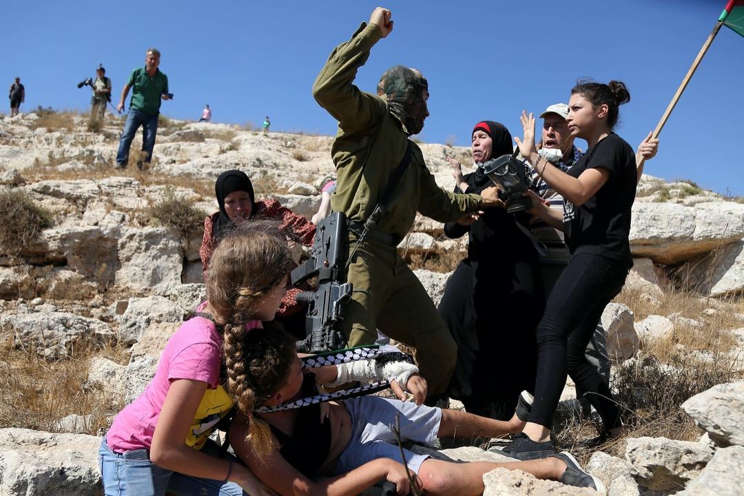 2015年8月,巴勒斯坦西岸城鎮拉馬拉,巴勒斯坦示威者與以色列部隊發生衝突期間,一名以色列士兵嘗試制服一名巴人小孩,旁人上前阻止。