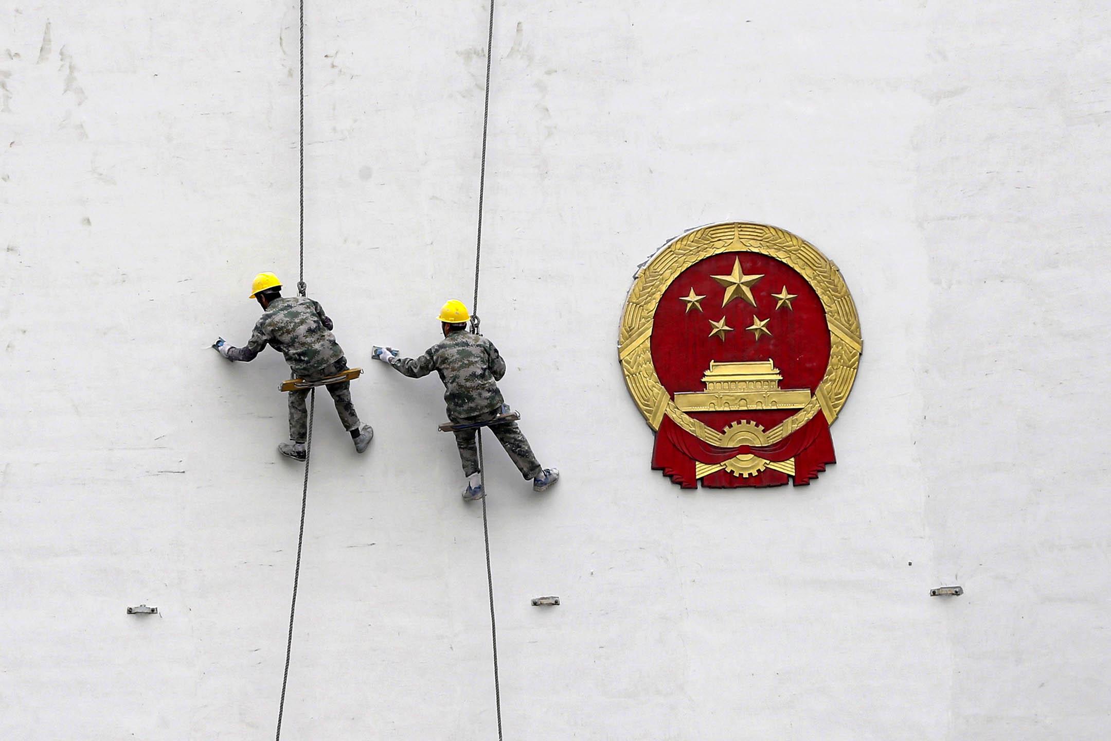 2016年3月26日中國杭州市,工人在大樓的牆壁上油漆。