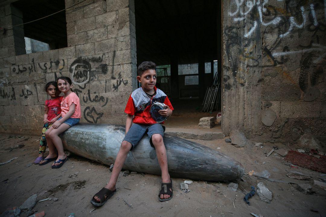 2021年5月19日,加沙地帶,巴勒斯坦兒童坐在一枚來自以色列未爆炸的導彈上。 攝:Mustafa Hassona/Getty Images