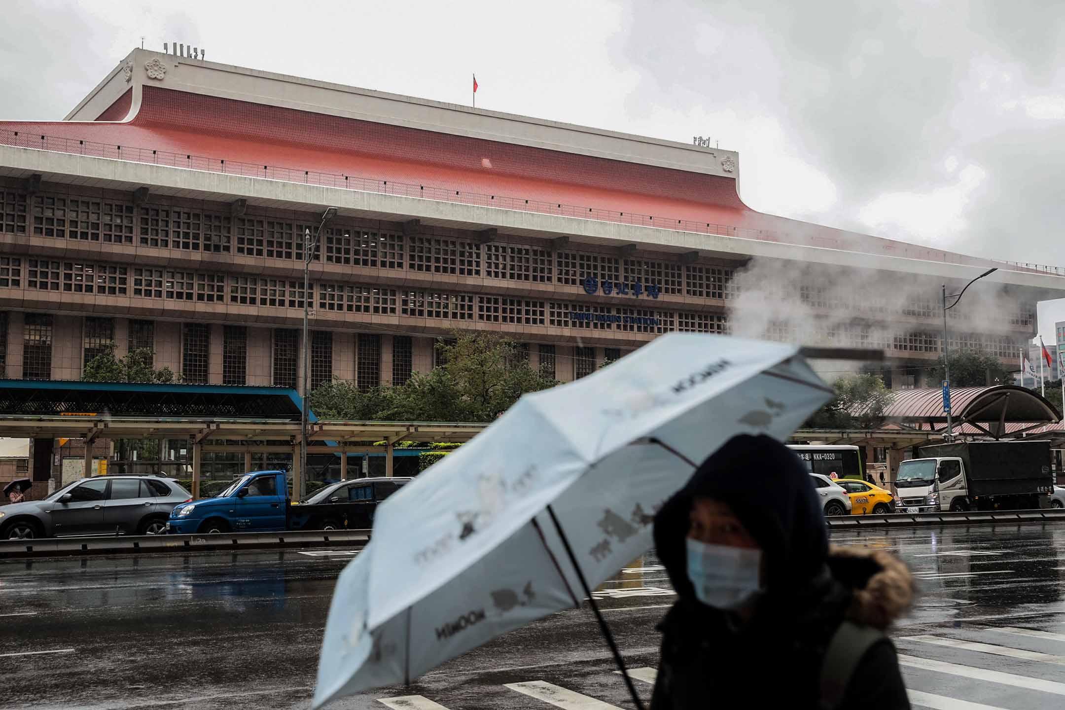 2021年1月11日台北,一名戴著口罩打著傘的行人經過台北車站。