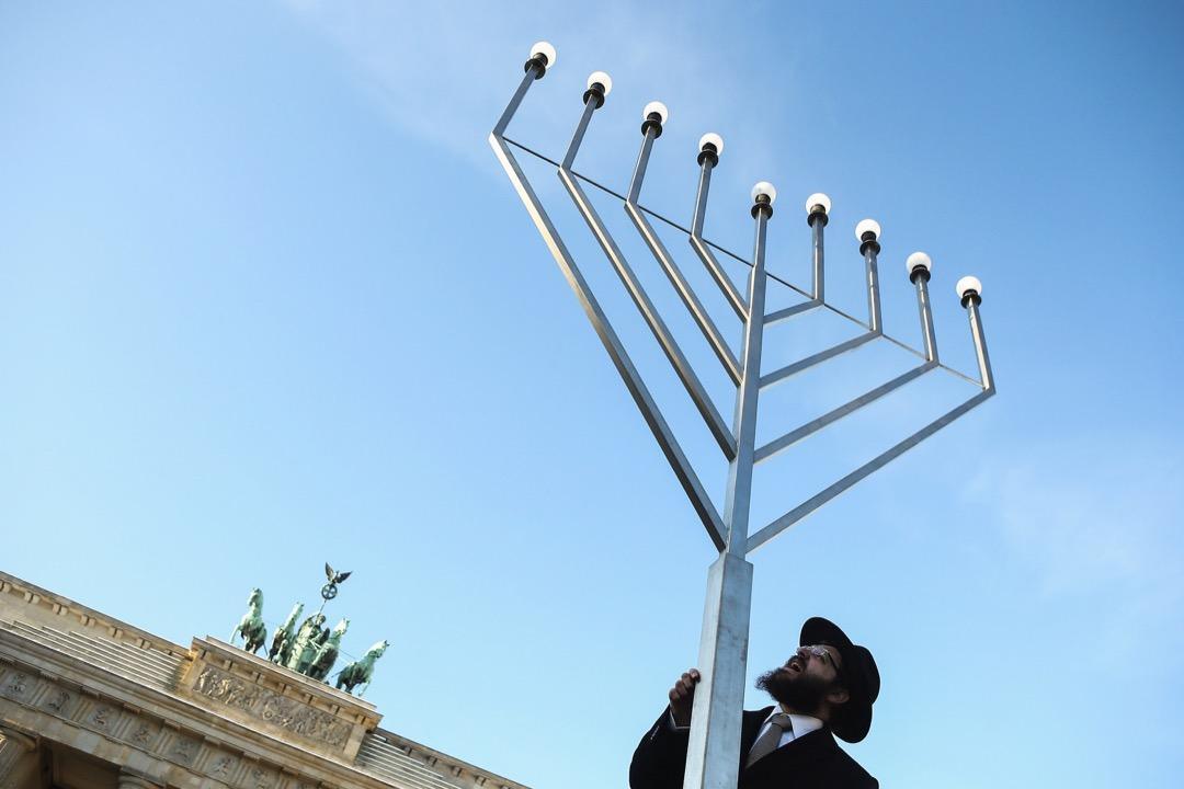 2012年12月,德國首都柏林,臨近猶太教節日光明節,數名拉比在勃蘭登堡門前豎起大型光明節燭台(Menorah)。