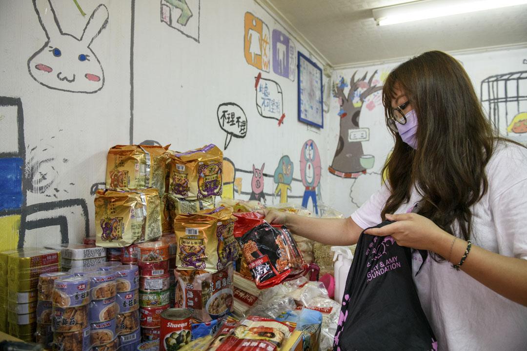 台灣社區實踐協會社工潘育欣將收到的食物分裝,派發給弱勢家庭。