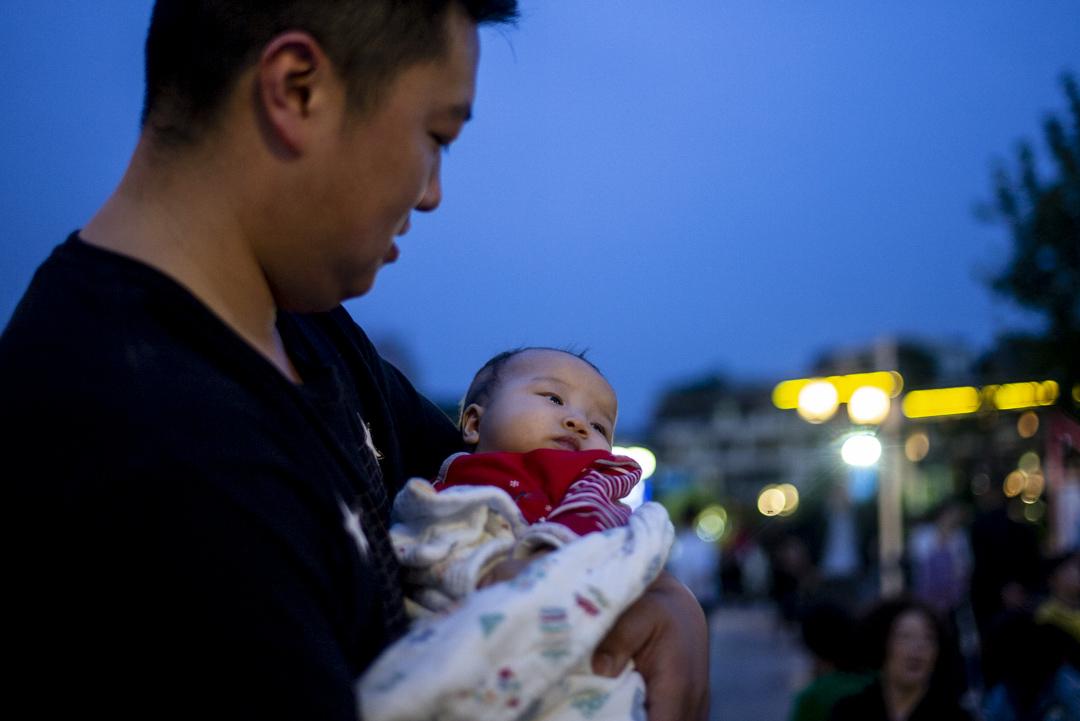 2021年5月29日,貴州遵義,爸爸手抱嬰兒在廣場上散步。 攝:林振東/端傳媒