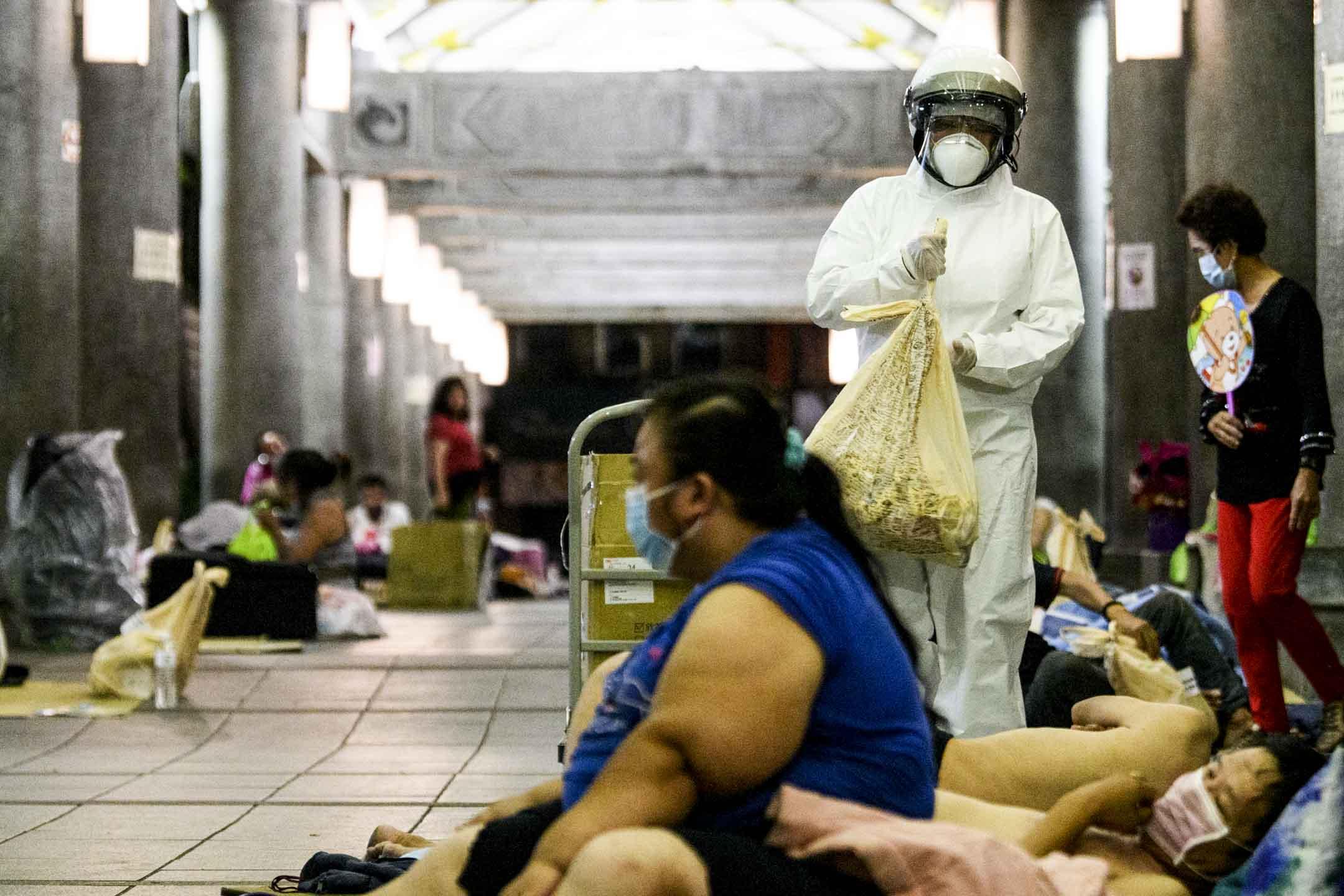 身穿全套防護衣的NGO芒草心社工為艋舺公園街友發放防疫物資包。 攝:李昆翰/端傳媒