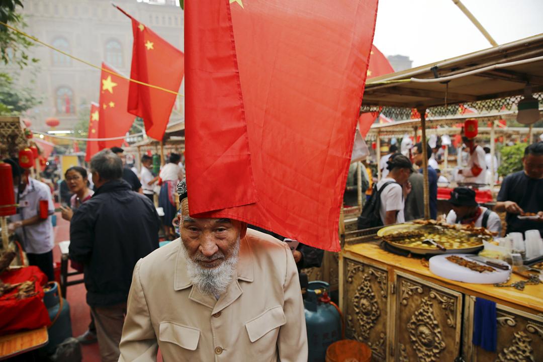 2018年11月29日在新疆喀什,一個市集掛滿了中國國旗,其中一面國旗擱在路過長者的額頭上。 攝:Thomas Peter / Reuters