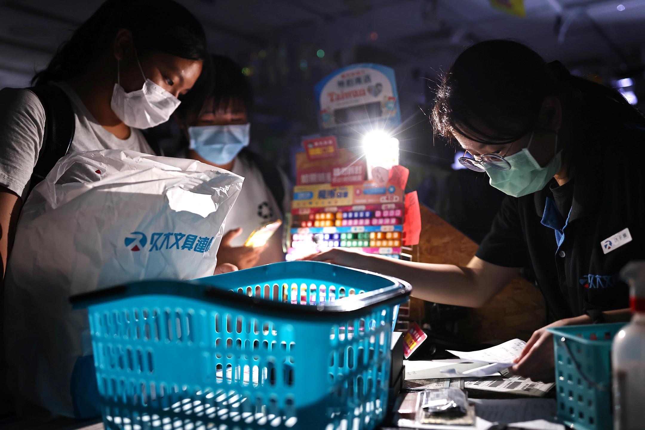 2021年5月13日台北,停電期間,一家商店內人們亮起手機燈付款。 攝:Ann Wang/Reuters/達志影像