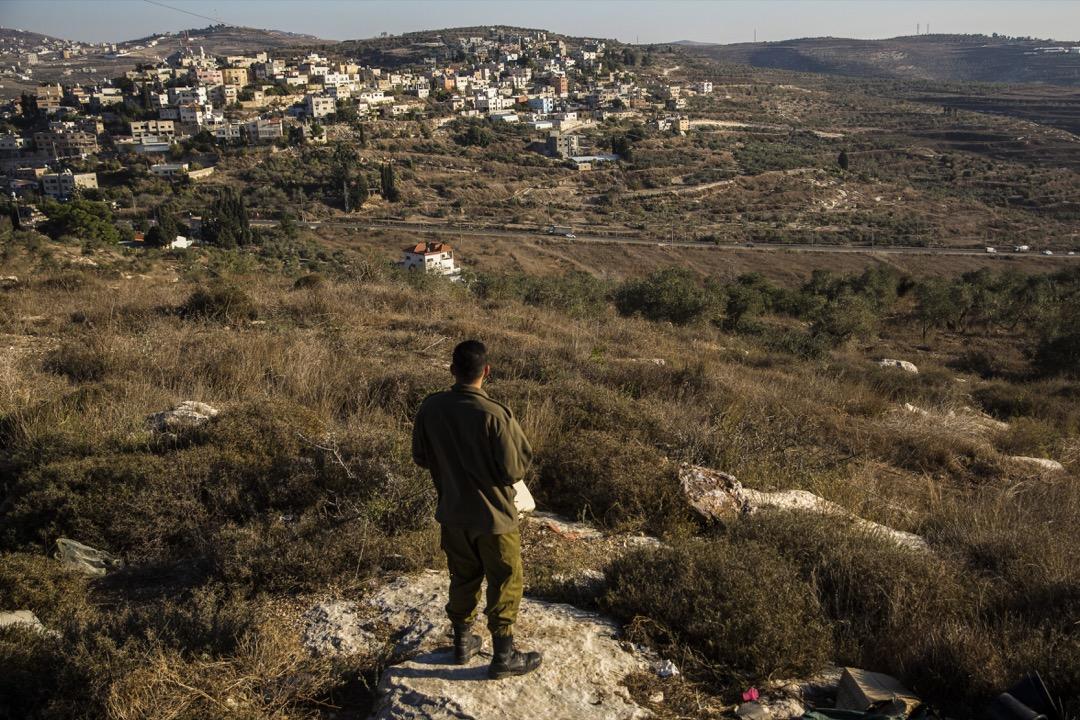 2019年11月,一名以色列士兵站在山丘上,望向遠處以色列在巴勒斯坦領土上佔領的定居點。