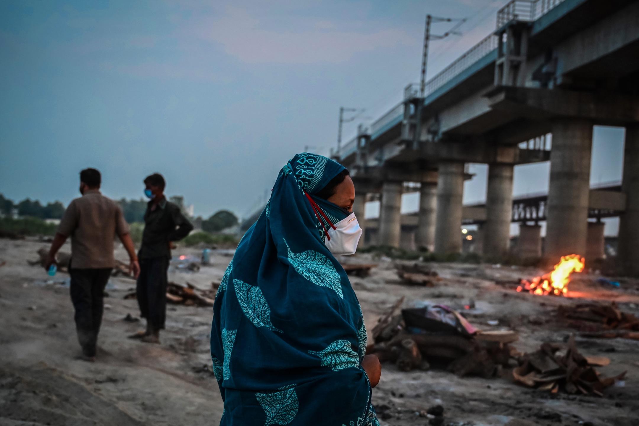 2021年5月6日,印度北方邦城市阿拉哈巴德,一名女子為一位因感染新冠病毒離世的家人進行火葬儀式後,步離火葬場。 攝:Ritesh Shukla/Getty Images