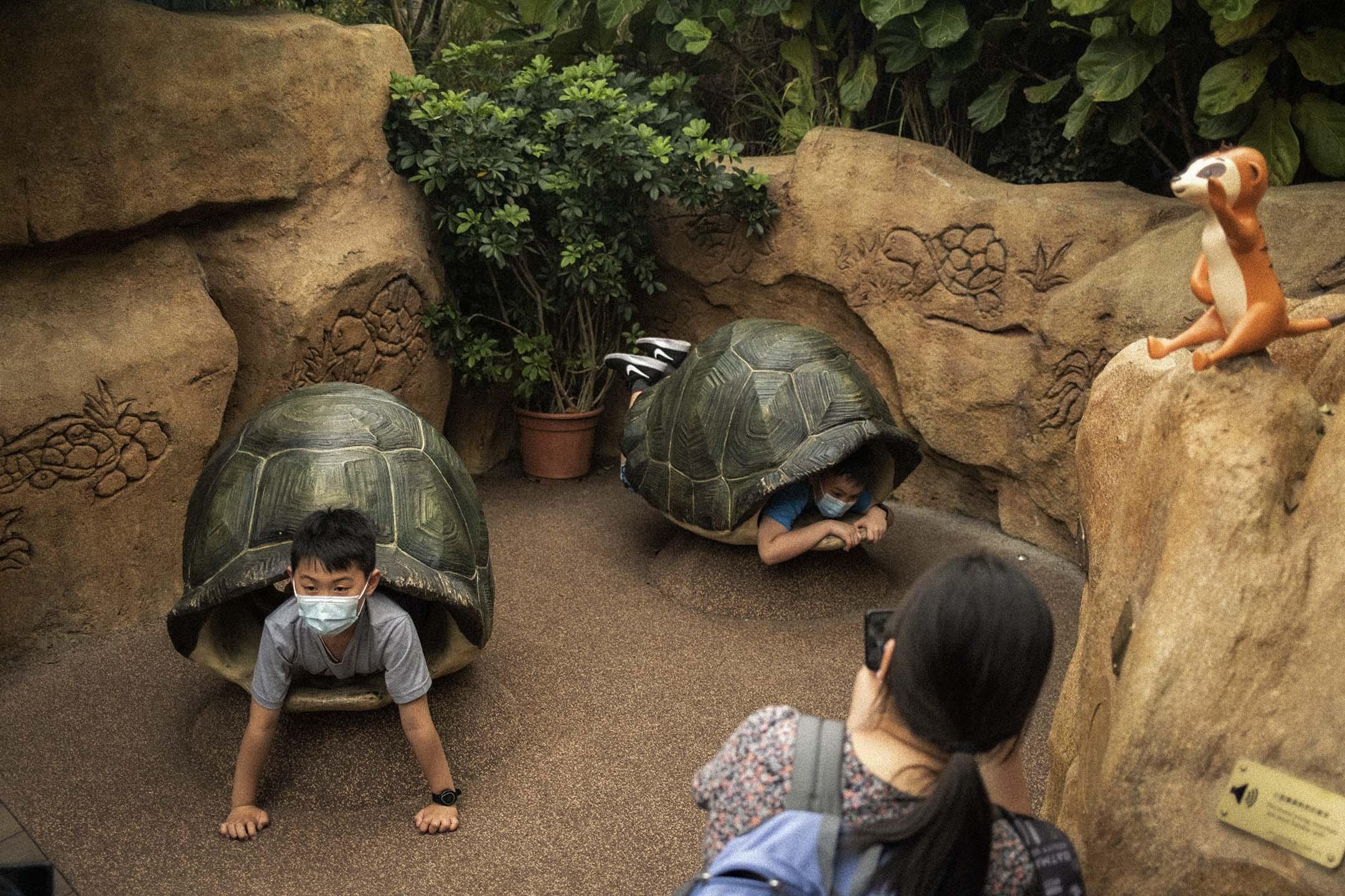 2021年4月1日海洋公園,兒童戴著口罩走進龜殼的擺設内。 攝:陳焯煇/端傳媒