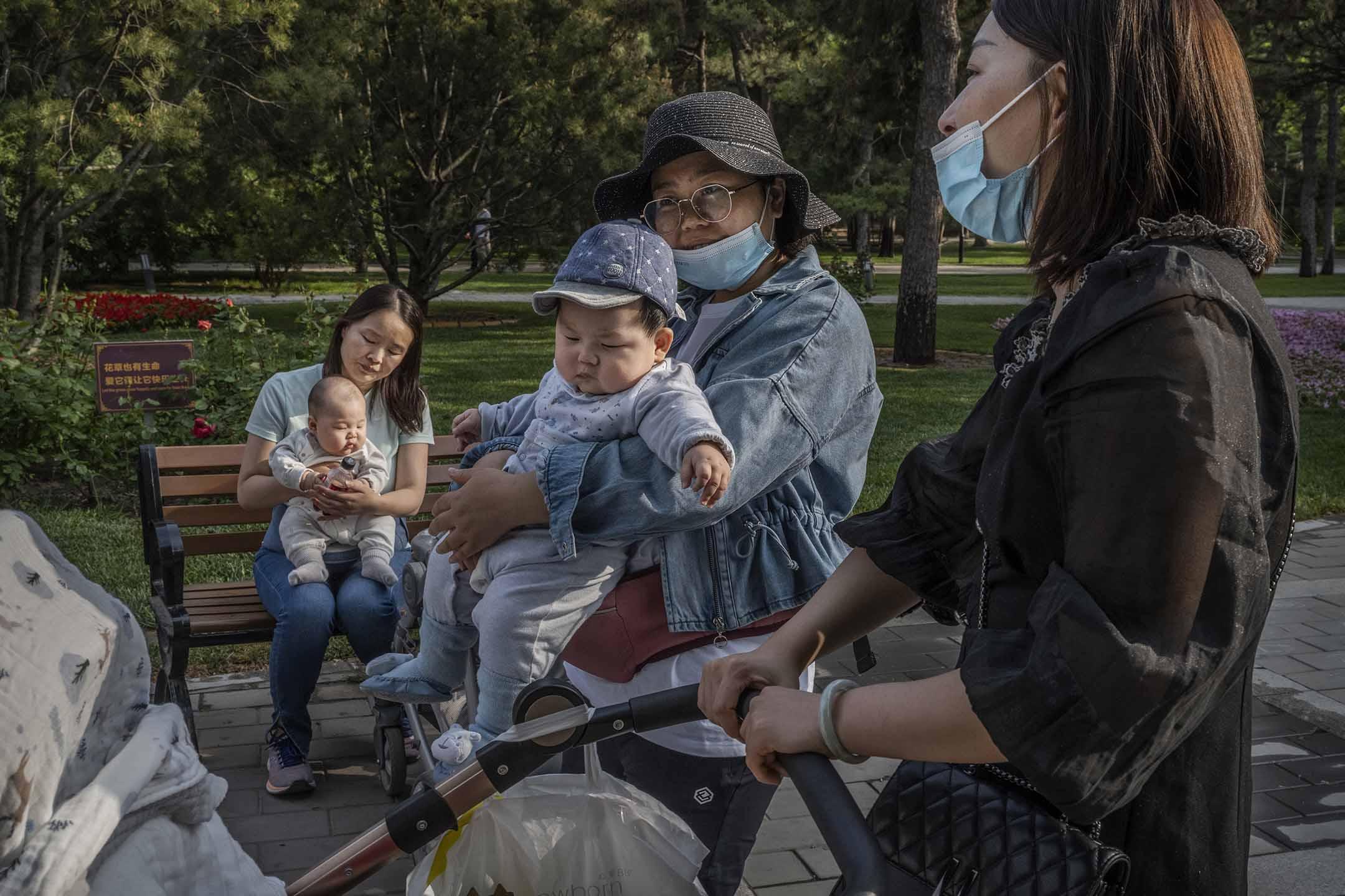2021年5月12日北京,婦女抱著孩子在一個公園內談話。 攝:Kevin Frayer/Getty Images