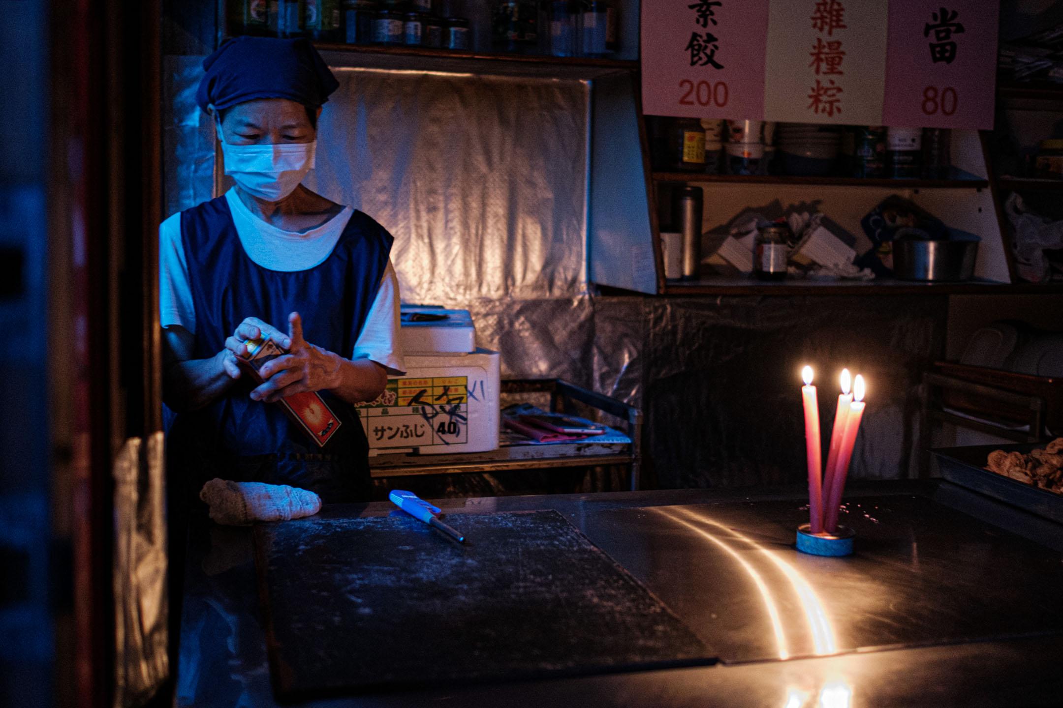 2021年5月13日台北,停電期間食店內一名職員點起蠟燭。 攝:唐佐欣/端傳媒