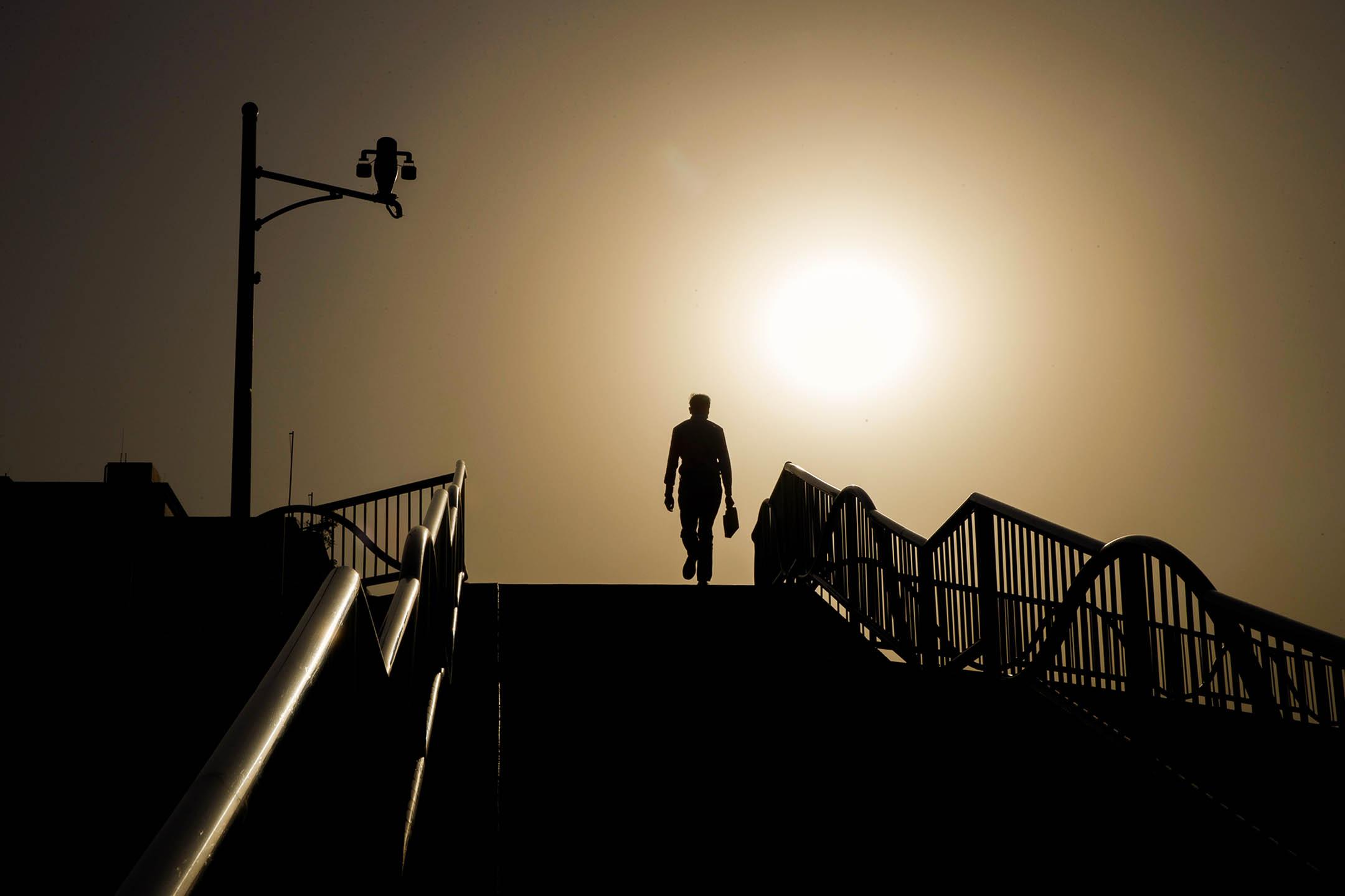2020年5月12日中國北京,一名男子走過有閉路電視攝像機的行人天橋。