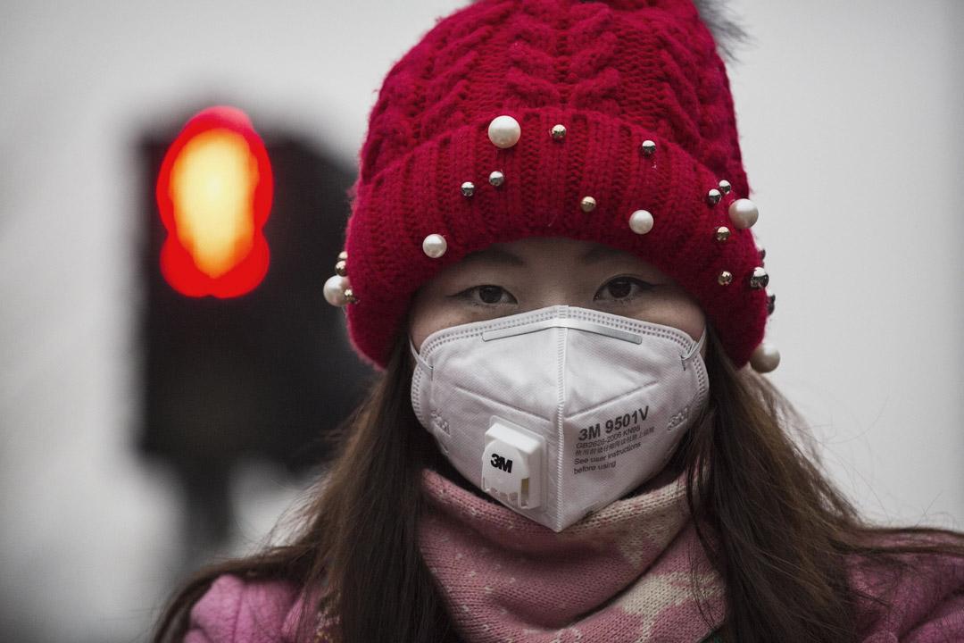 北京一名女士戴著口罩免受空氣的污染。 攝:Kevin Frayer/Getty Images
