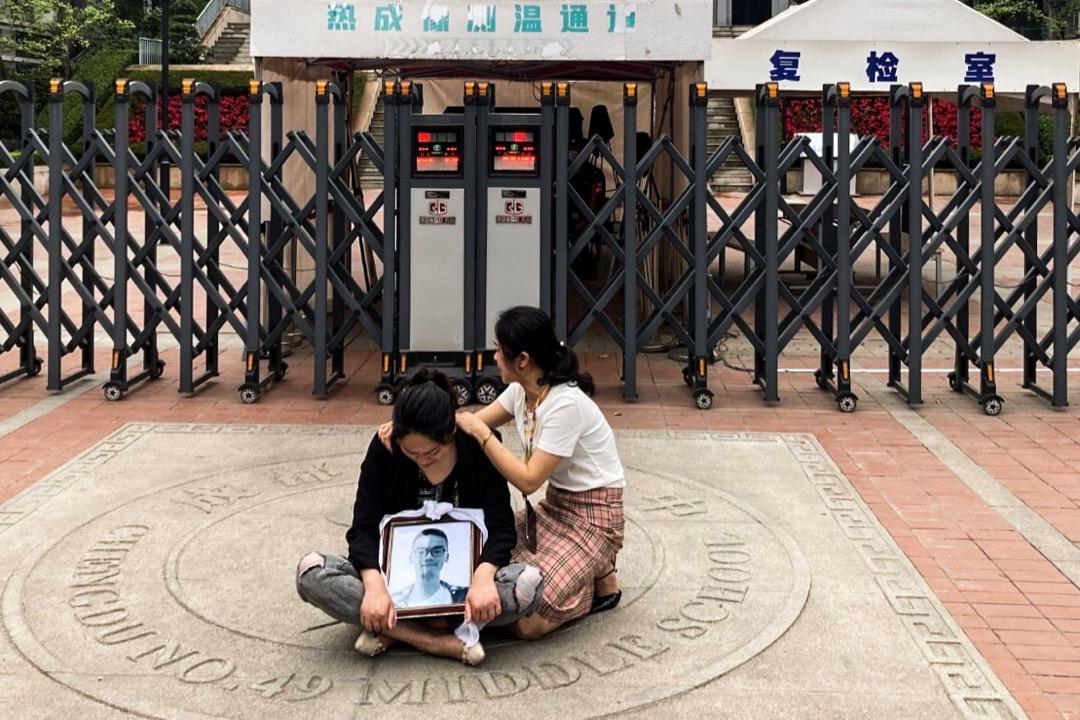 2021年5月11日,成都49中門外,墮樓身亡學生林唯麒的母親抱著兒子的遺照坐在地上。