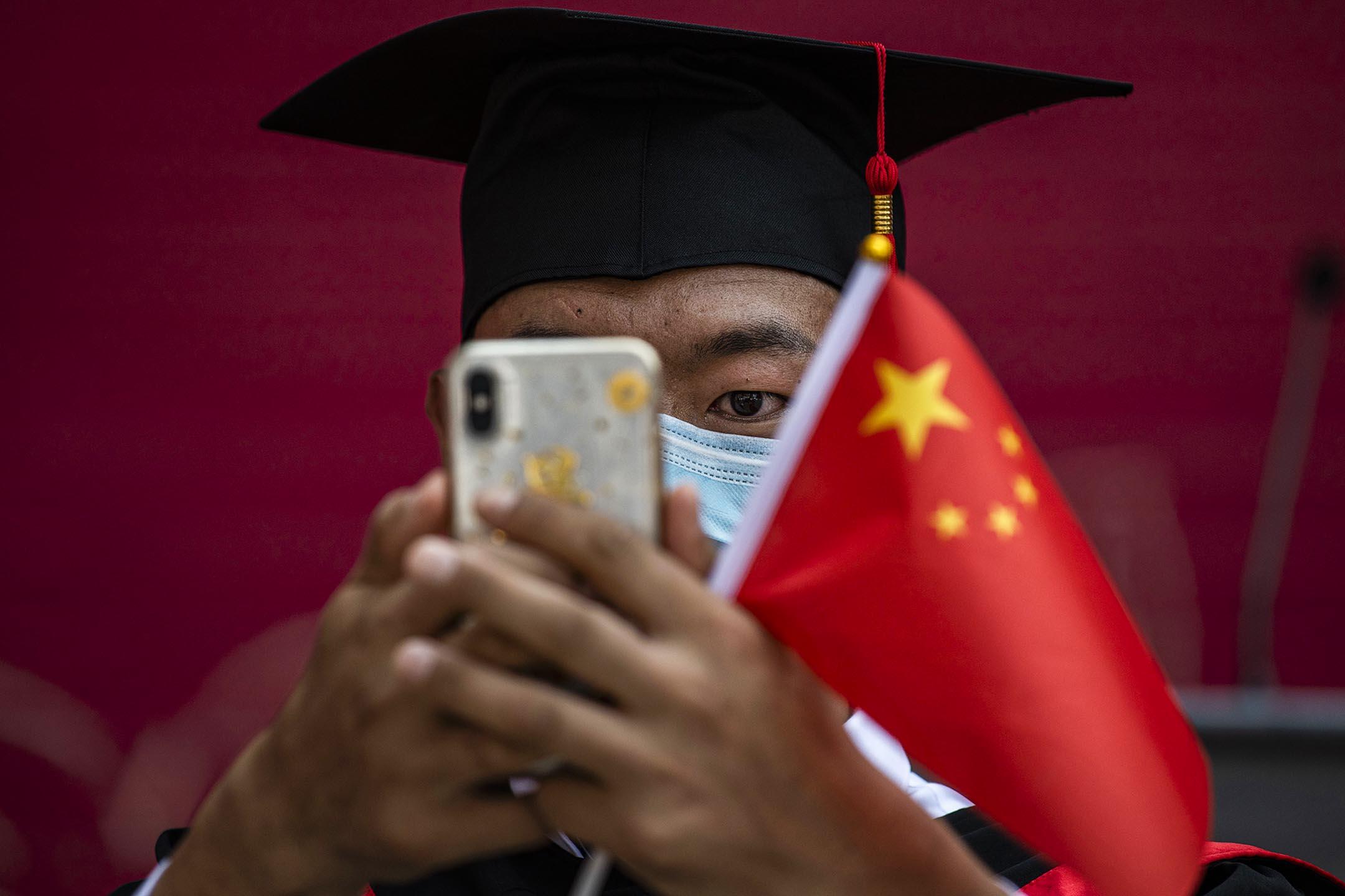 2020年6月30日在中國北京,中國人民大學的學生拿著一面國旗參加畢業典禮。