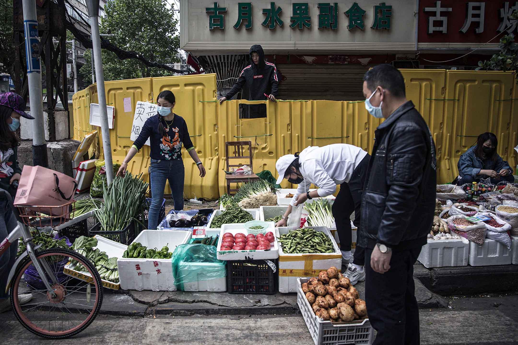 2020年4月17日武漢,路障前商販在出售蔬菜,疫情期間,社區被圍封以控制居民進出。