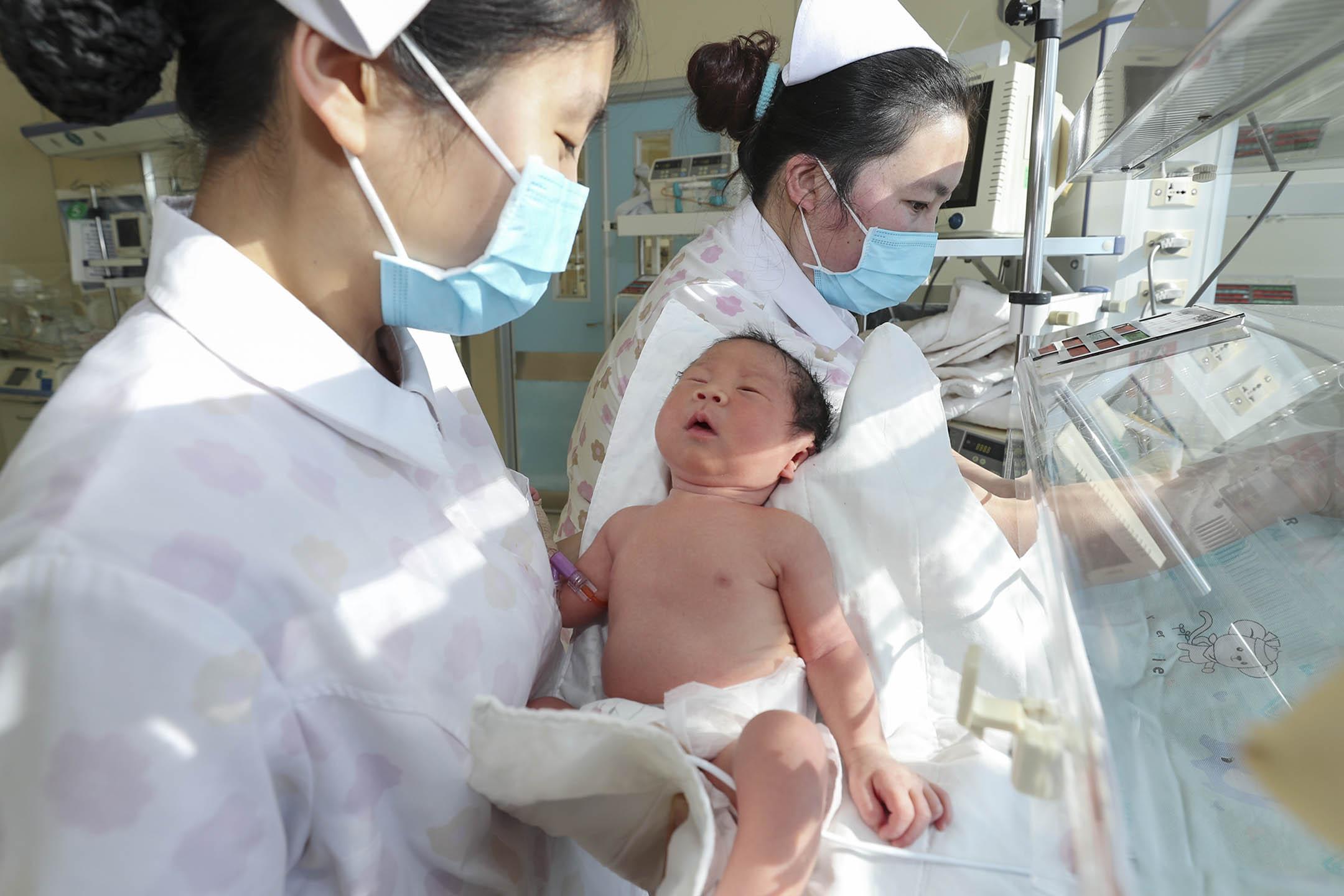 2020年1月1日中國連雲港市,兩名護士在新生嬰兒監護室照顧一名早產嬰兒。
