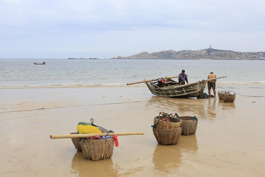 平潭島兩名漁民在海灘上的船。