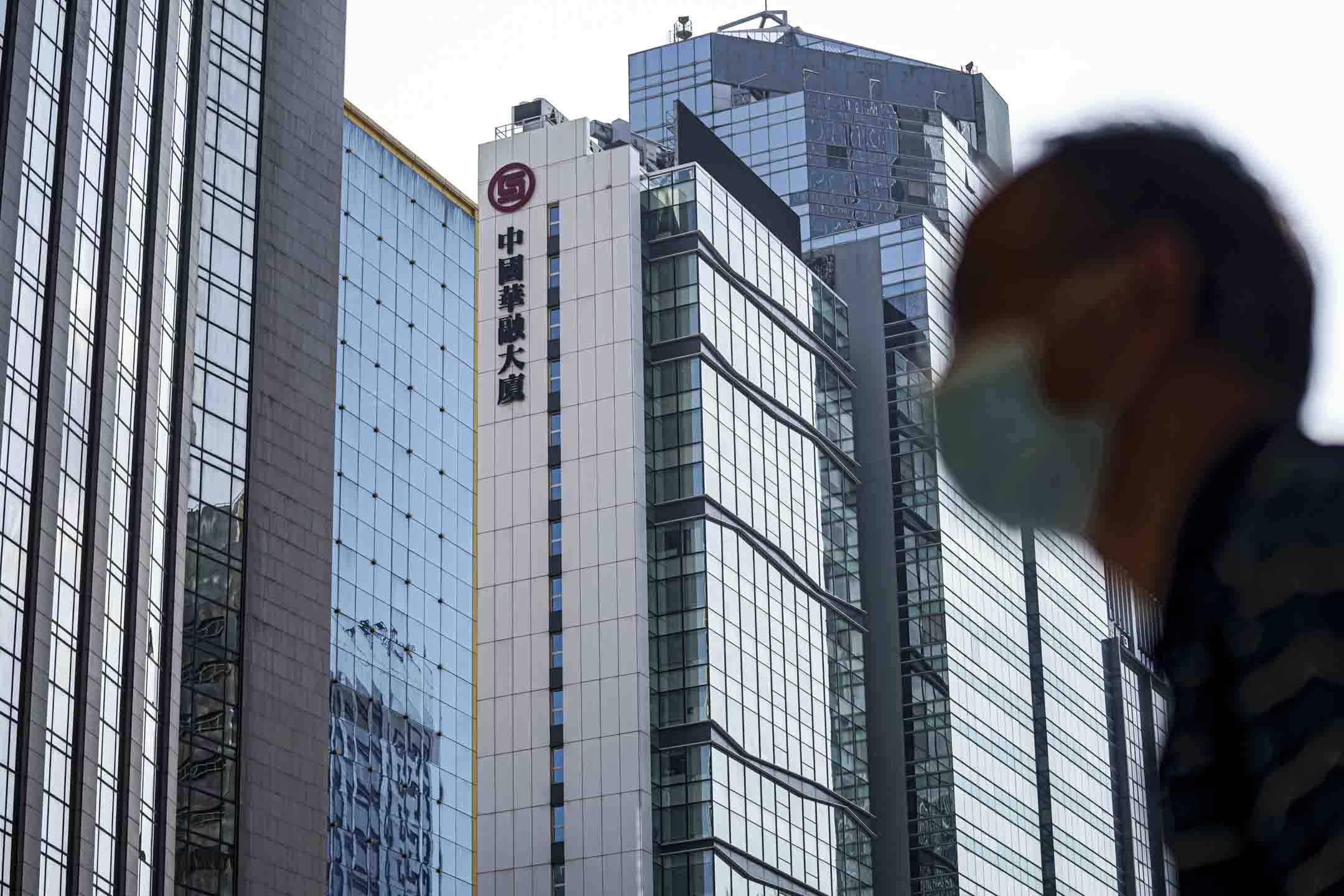 2021年2月21日,香港,一名行人經過中國華融大廈。 攝:Lam Yik/Bloomberg via Getty Images