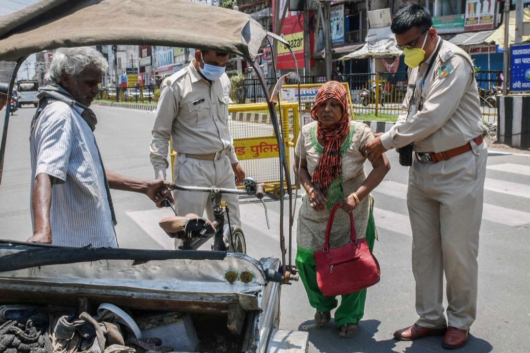 2020年5月11日,印度城市蘭契,一名警員協助一位長者到三輪車上。