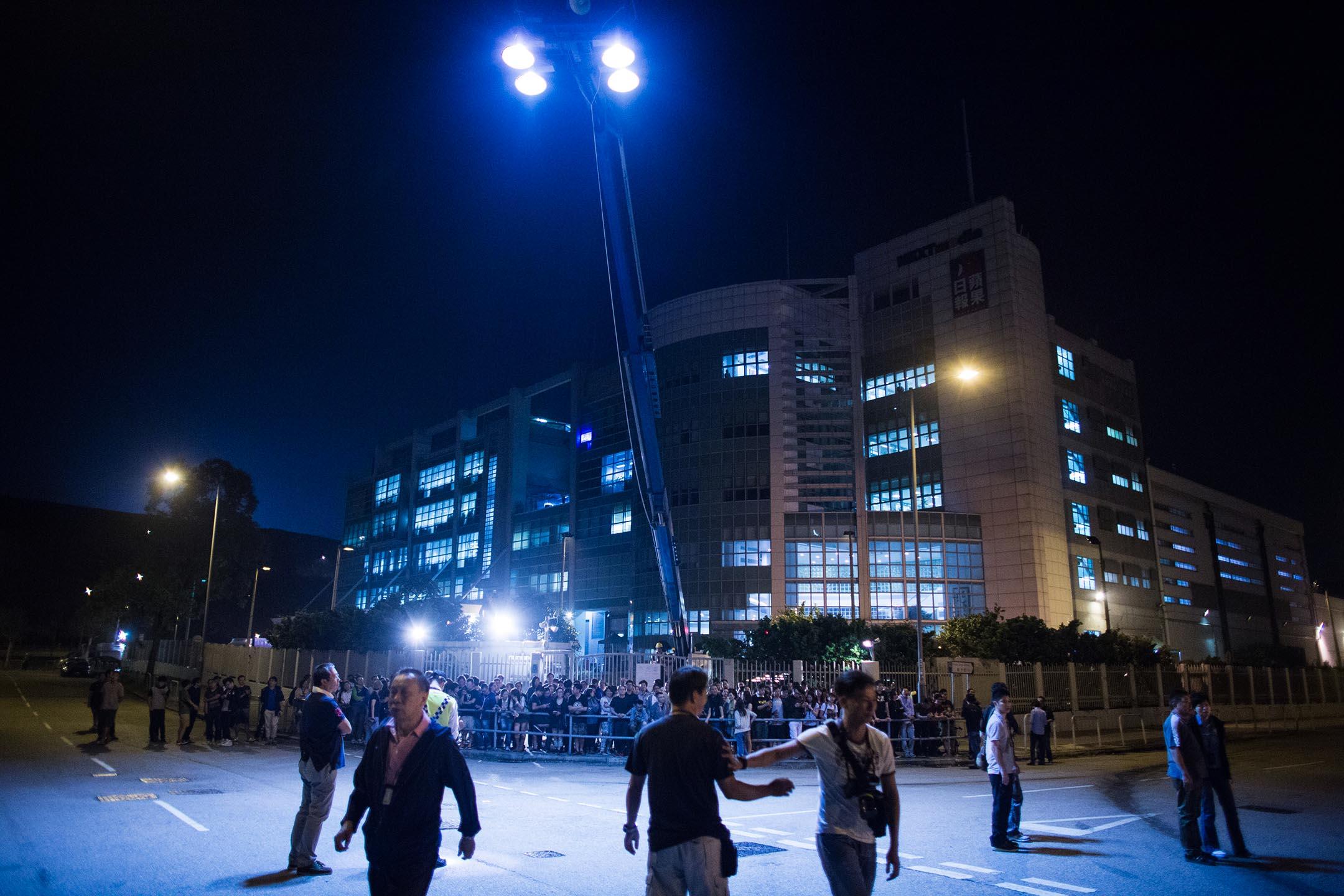 2014年10月15日香港,有市民包圍將軍澳區蘋果日報大樓,阻止報紙出版,蘋果員工築成人鍊,護送貨車離開。 攝:Lam Yik Fei/Bloomberg via Getty Images