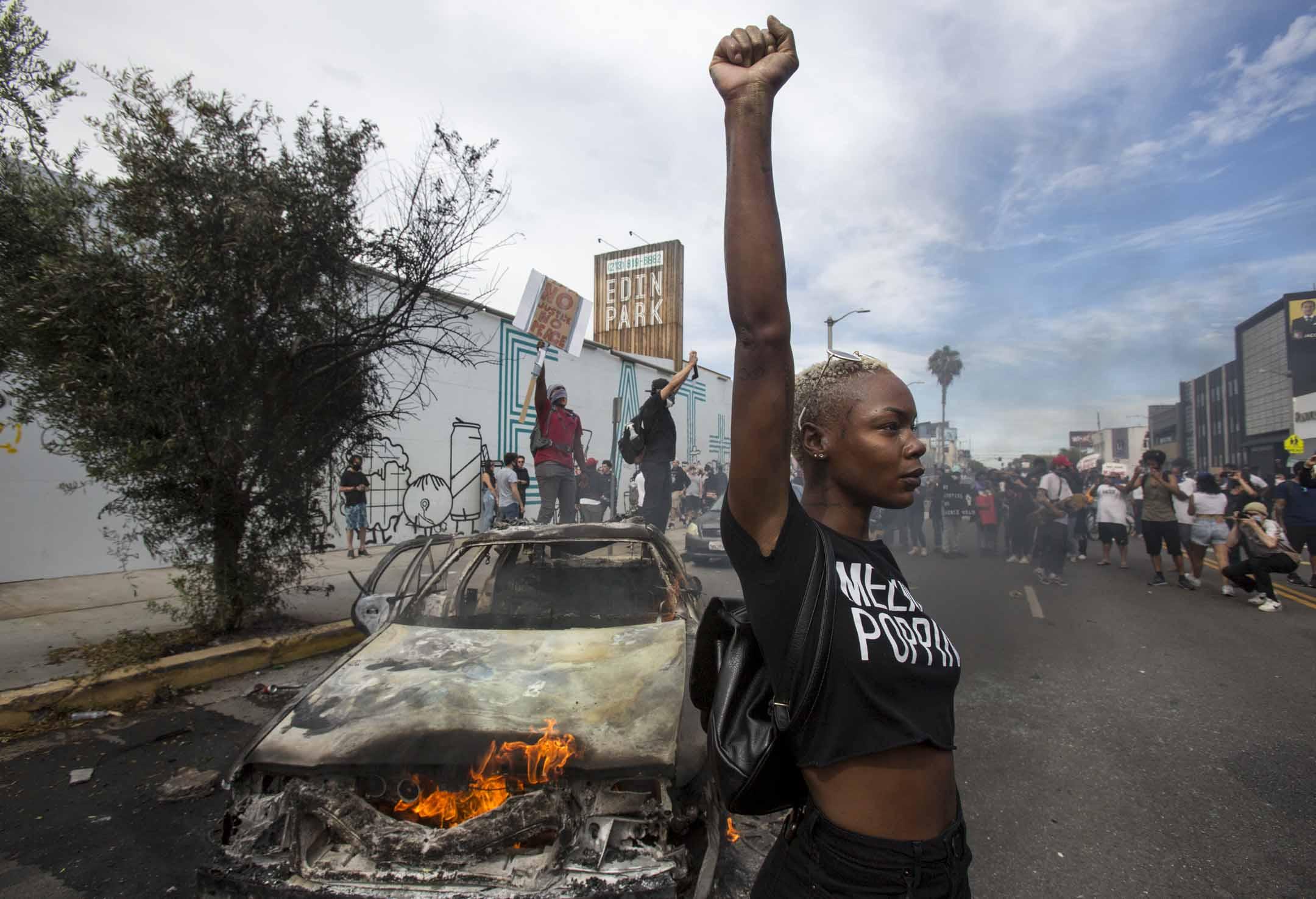 2020年5月30日,美國加州城市洛杉磯,有示威悼念明尼亞波利斯被警察粗暴壓頸致死的黑人男子 George Floyd,一名示威者在一輛焚燒中的警車前舉起拳頭。