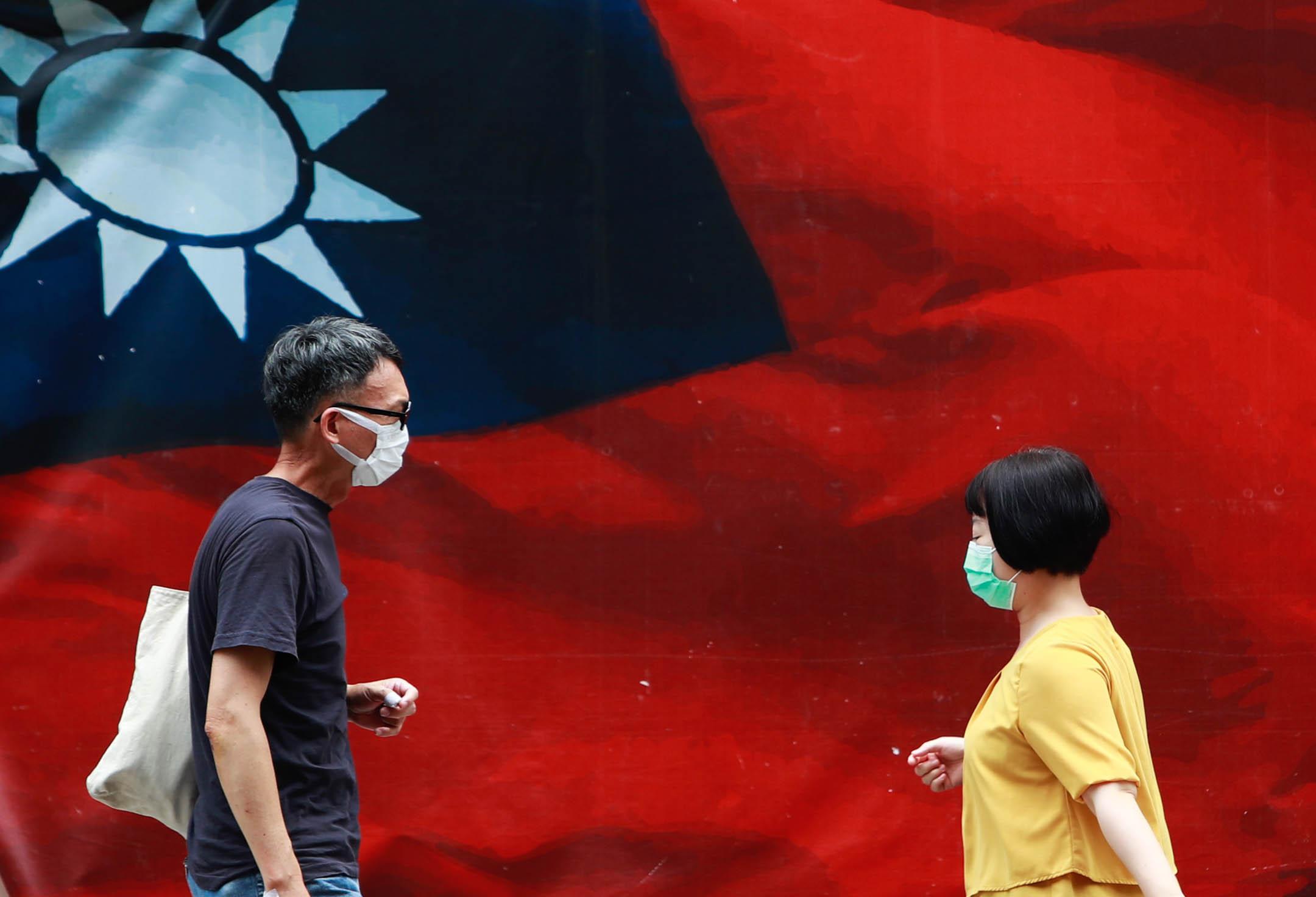 2021年5月17日台灣台北,台灣增加了 333 例國內病例和 2 例進口病例,人們戴著口罩走過台灣國旗。 攝:Ceng Shou Yi/NurPhoto via Getty Images