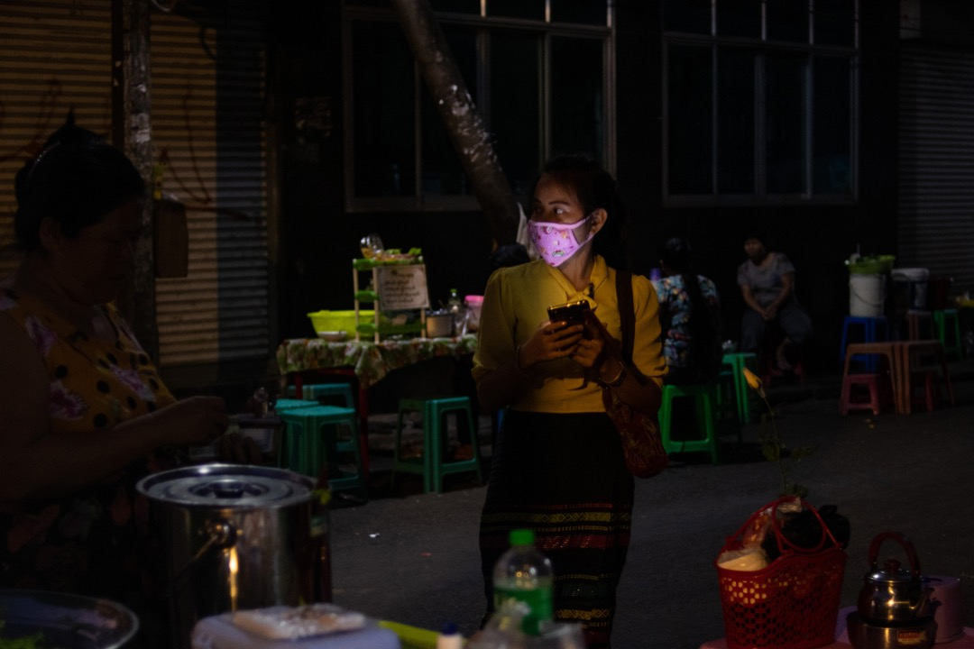 緬甸仰光,一名女子在市場裏看手機。