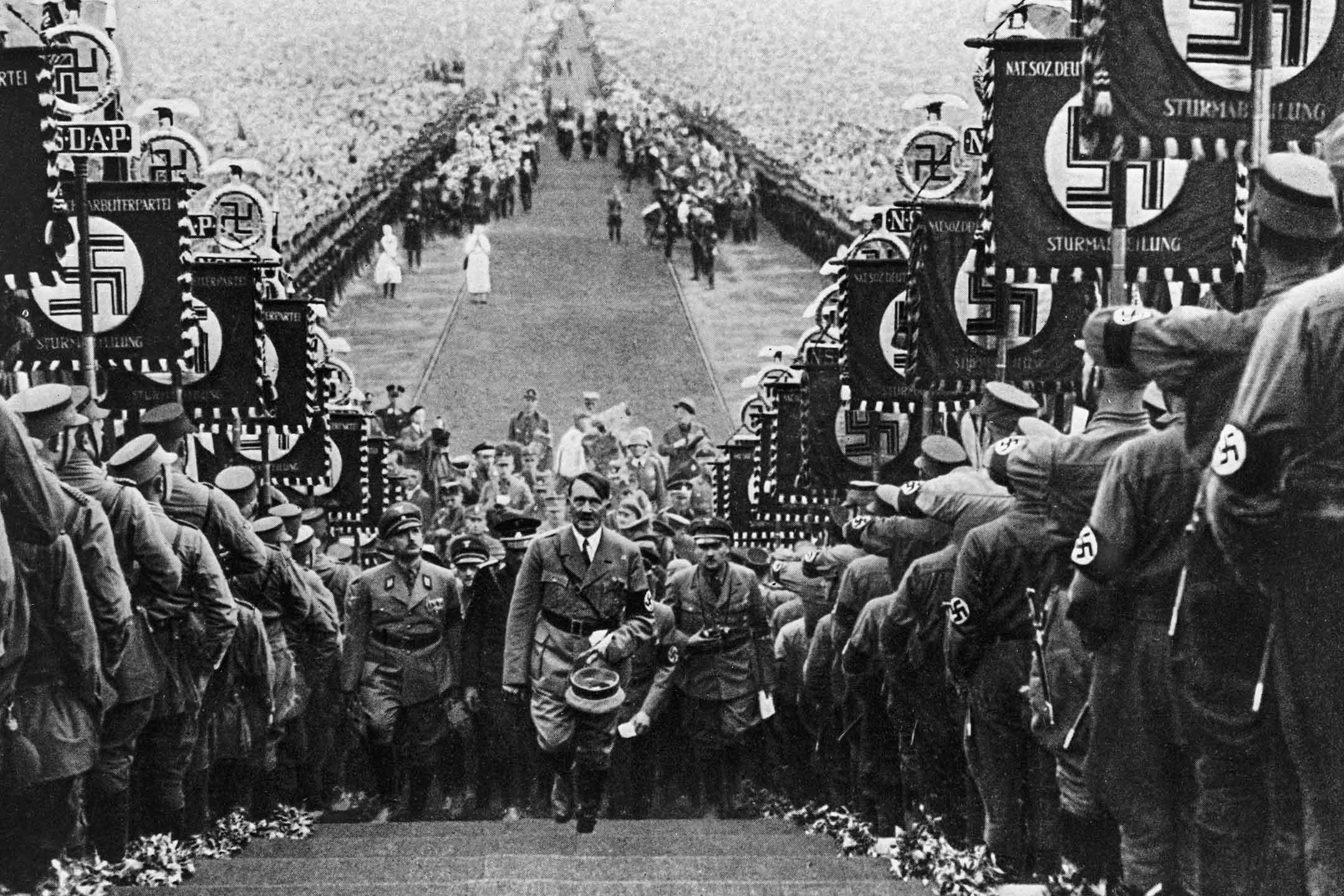 德國獨裁者希特勒登上台階,兩側是舉著旗幟展示著納粹萬字符的隊伍。