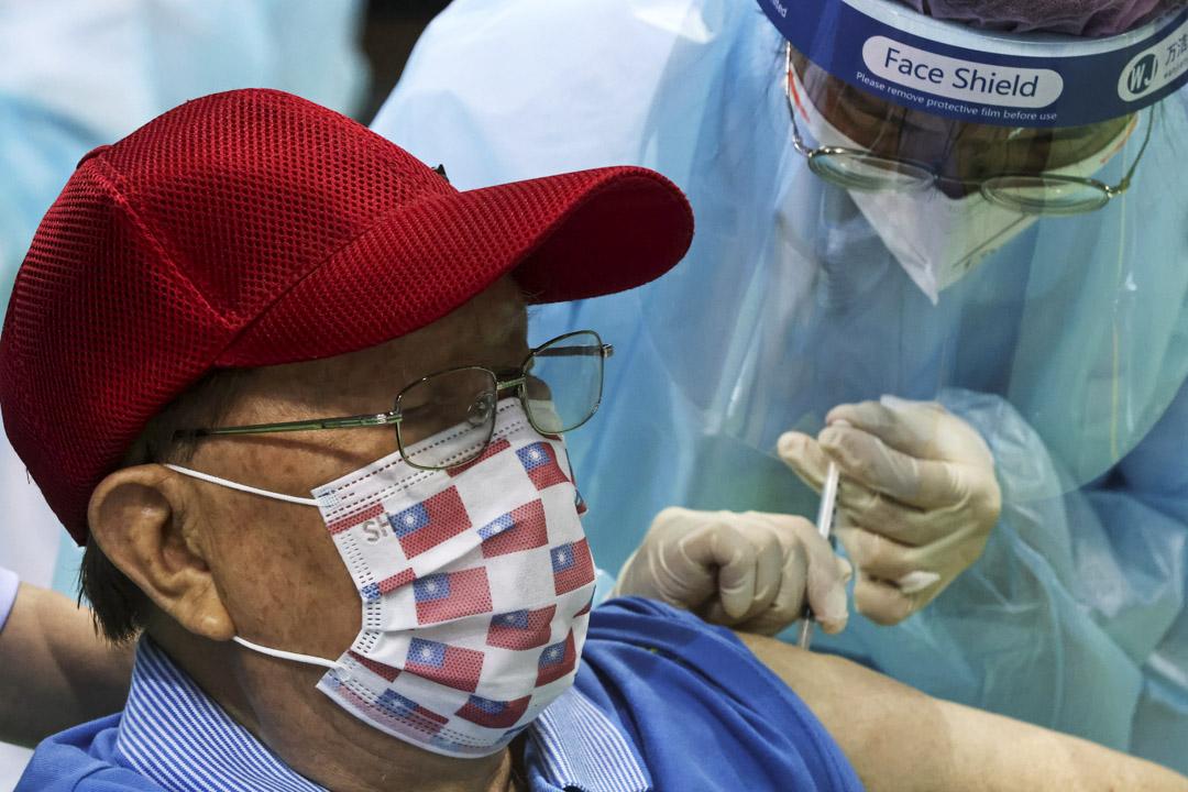2021年6月15日台灣新北市的一個體育場,一名醫務人員在為老年人接種疫苗。 攝:Ann Wang/Reuters/達志影像