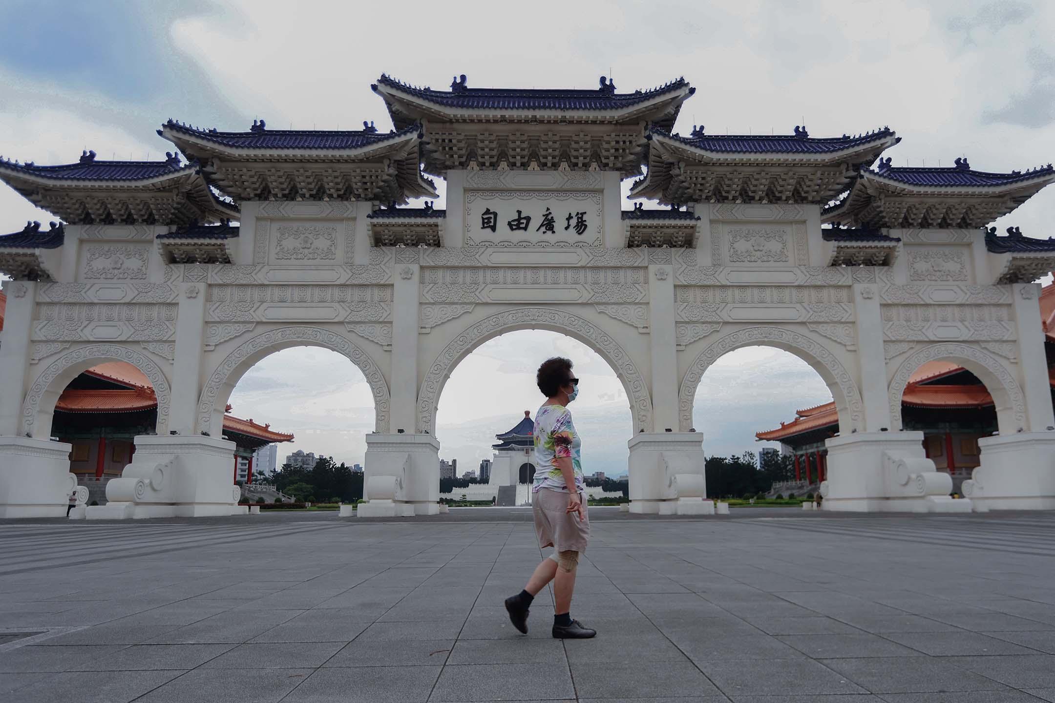 2021年5月21日台灣台北,2019冠狀病毒病例激增之後,戴著口罩的人們走過自由廣場。