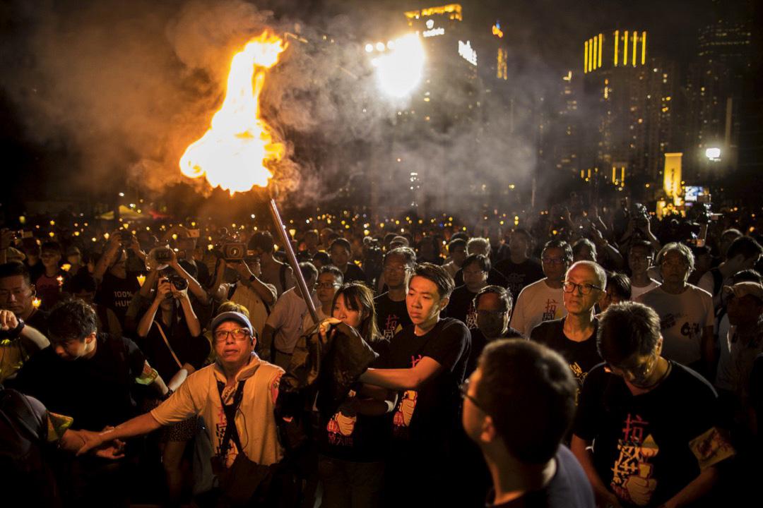 2018年6月4日,「悼六四、抗威權」燭光晚會上,支聯會常委與年青人燃點火炬步向舞台。