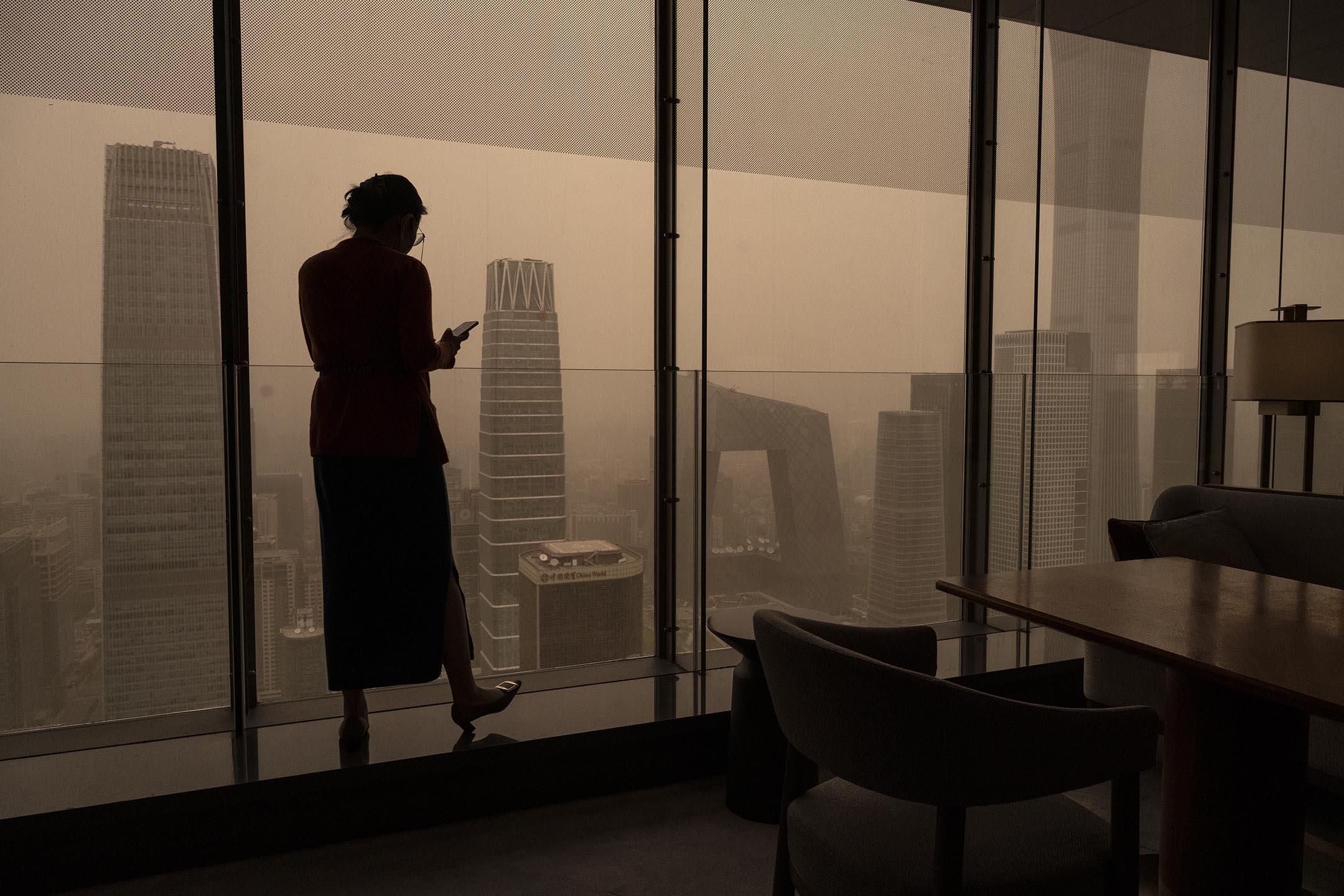 2021年4月15日中國北京,沙塵暴期間,一名婦女從窗戶向外看。 攝:Kevin Frayer/Getty Images