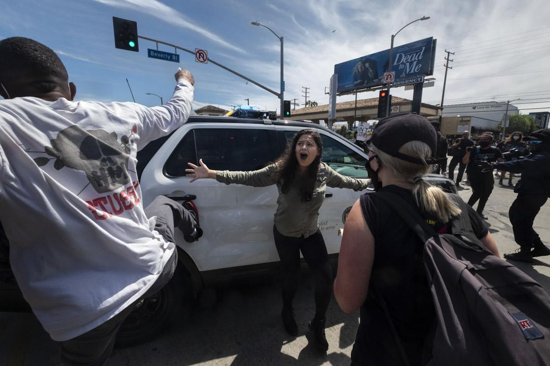 2020年5月30日,美國加州城市洛杉磯,有示威悼念明尼亞波利斯被警察粗暴壓頸致死的黑人男子 George Floyd,一名示威者嘗試阻止其他示威者破壞一輛警車。