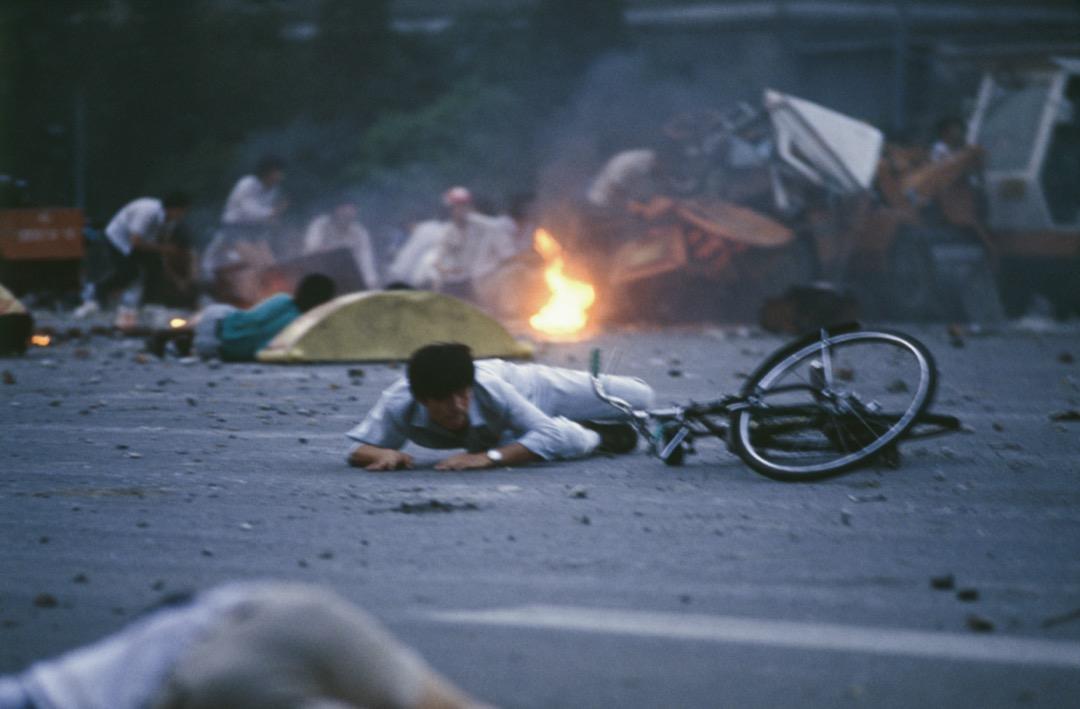 1989年6月4日凌晨,北京,解放軍在天安門廣場一帶向市民開槍,有市民趴在地上躲避。