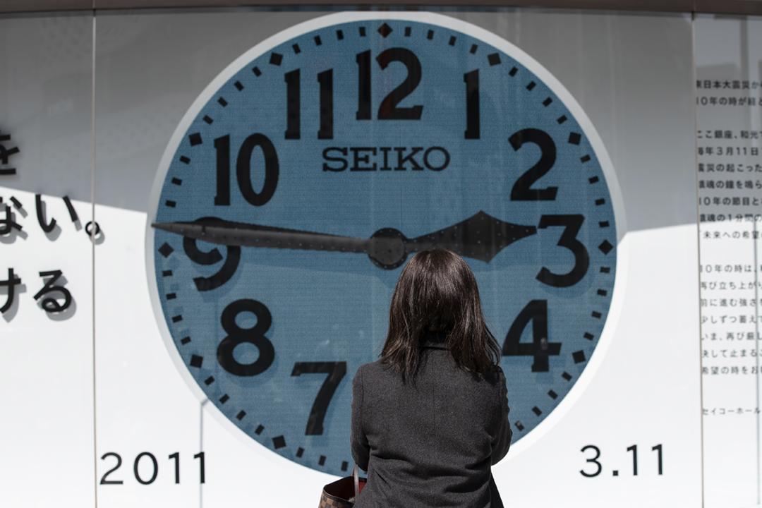 2021年3月11日在日本東京,一名女途人駐足觀看一個大型時鐘,時鐘指針設置在2011年3月11日下午2時46分,即日本東北部大地震發生的一刻。該場地震引發海嘯,令福島第一核電廠受到破壞,導致核災難。 攝:Takashi Aoyama / Getty Images