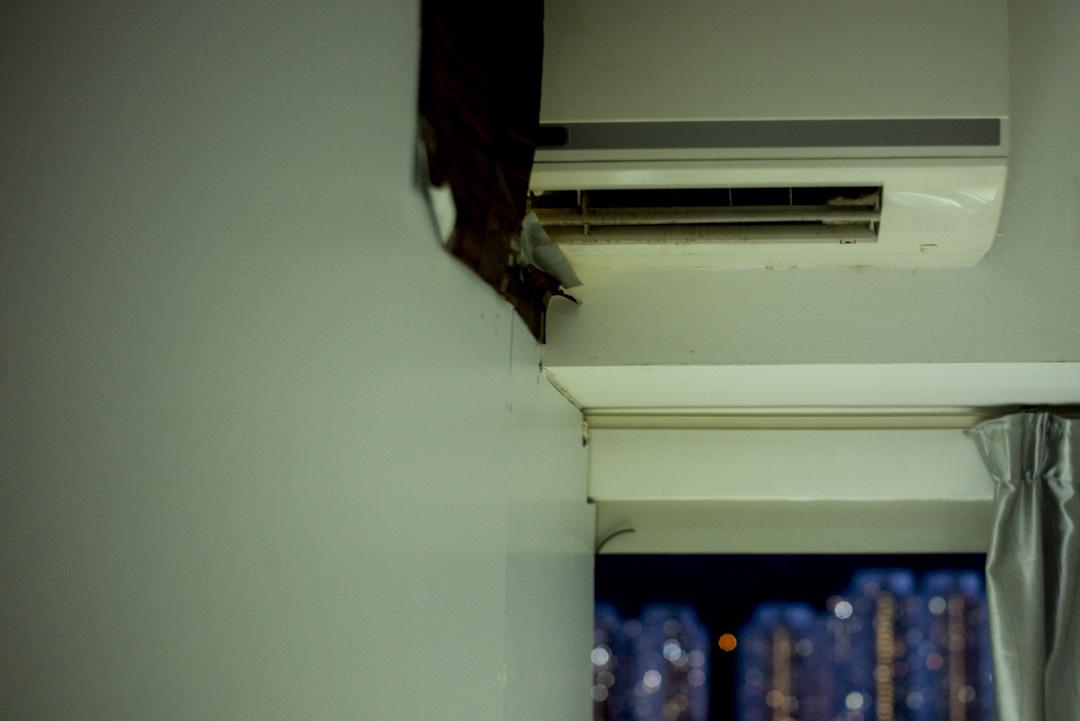 兩個單人劏房單位共用一台冷氣機,一人一部遙控,冷氣機穿過兩房中間的白色木板。