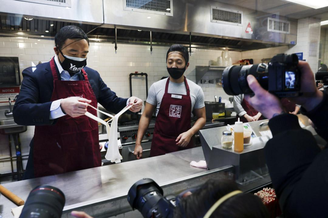 2021年3月5日紐約,紐約市市長候選人楊安澤(左)於 唐人街的食店與店主一起拉麵條。