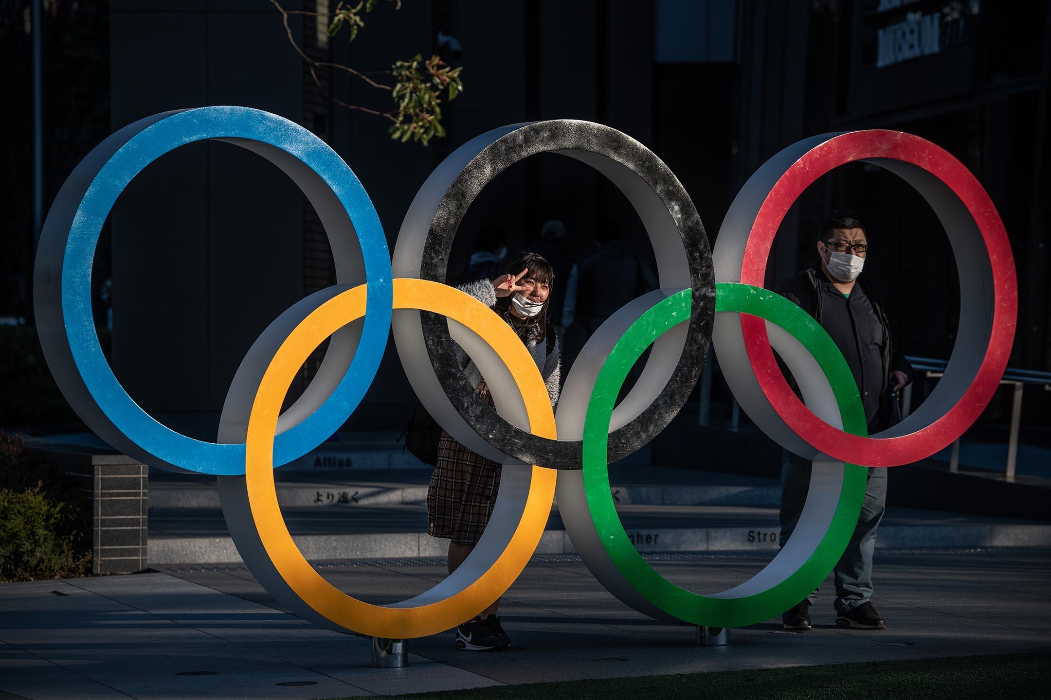2020年3月24日日本東京,戴著口罩的人們在奧運五環旁拍照。 攝:Carl Court/Getty Images