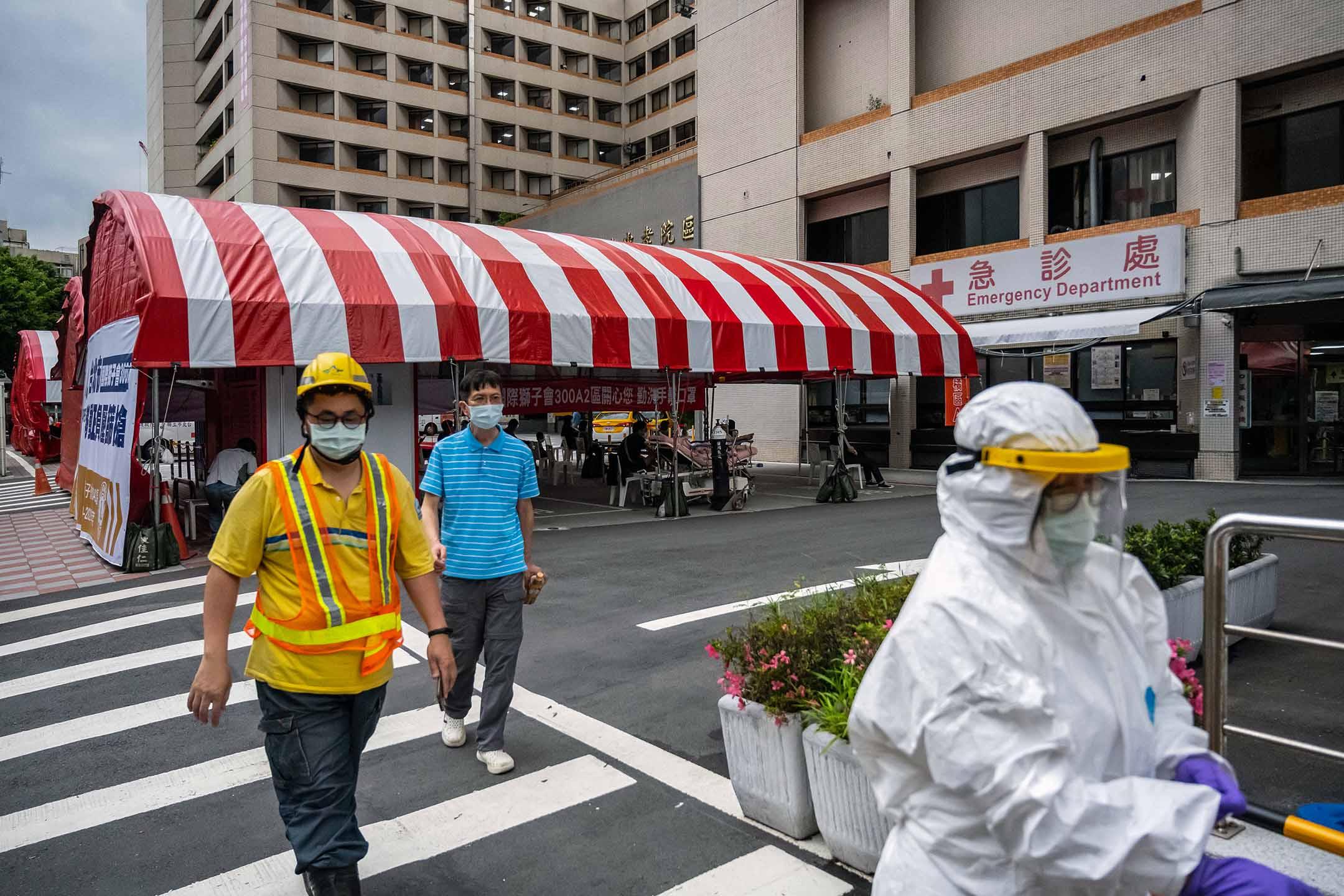 2021年6月3日台灣台北,戴著防護口罩的行人走過一家醫院外搭建的帳篷。