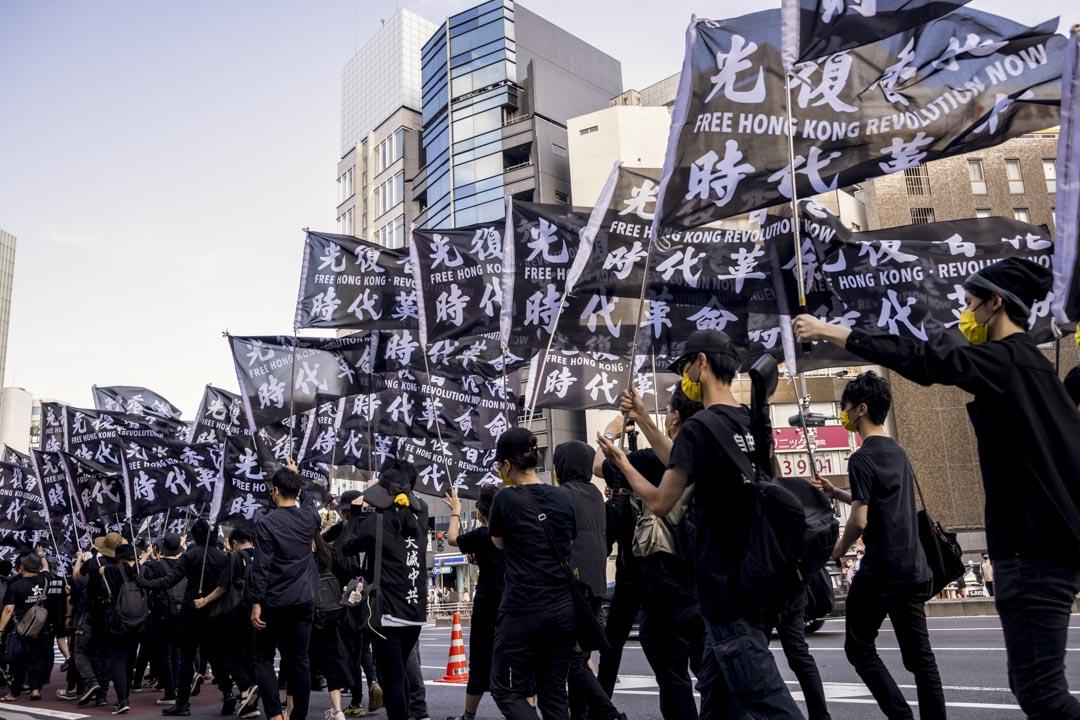 2021年6月12日,日本東京,遊行人士高舉「光時」旗幟於6.12 衝突兩周年的時候參與遊行。