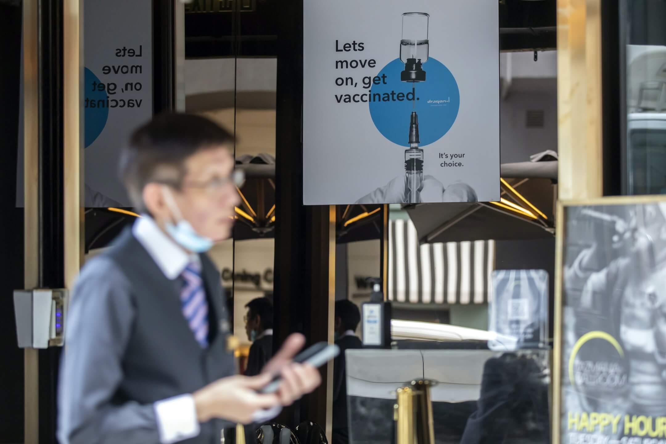 2021年4月19日,香港蘭桂坊的酒吧門外,貼上一張鼓勵市民接種疫苗的海報。 攝:Paul Yeung/Bloomberg via Getty Images