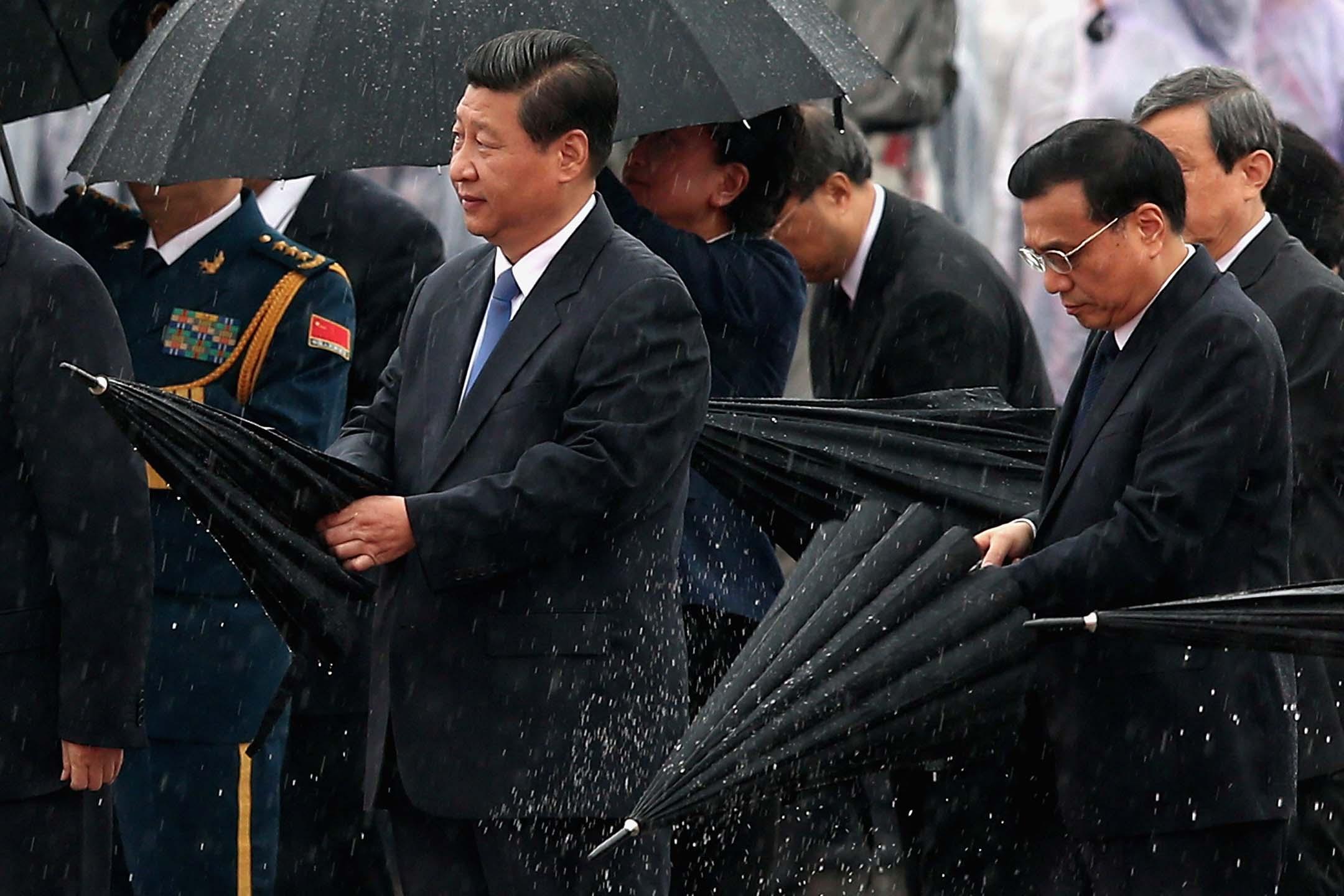 2013年10月1日中國北京,慶祝中華人民共和國成立 64 週年,中國國家主席習近平(左)和李克強總理(右)在向人民英雄紀念碑鞠躬。